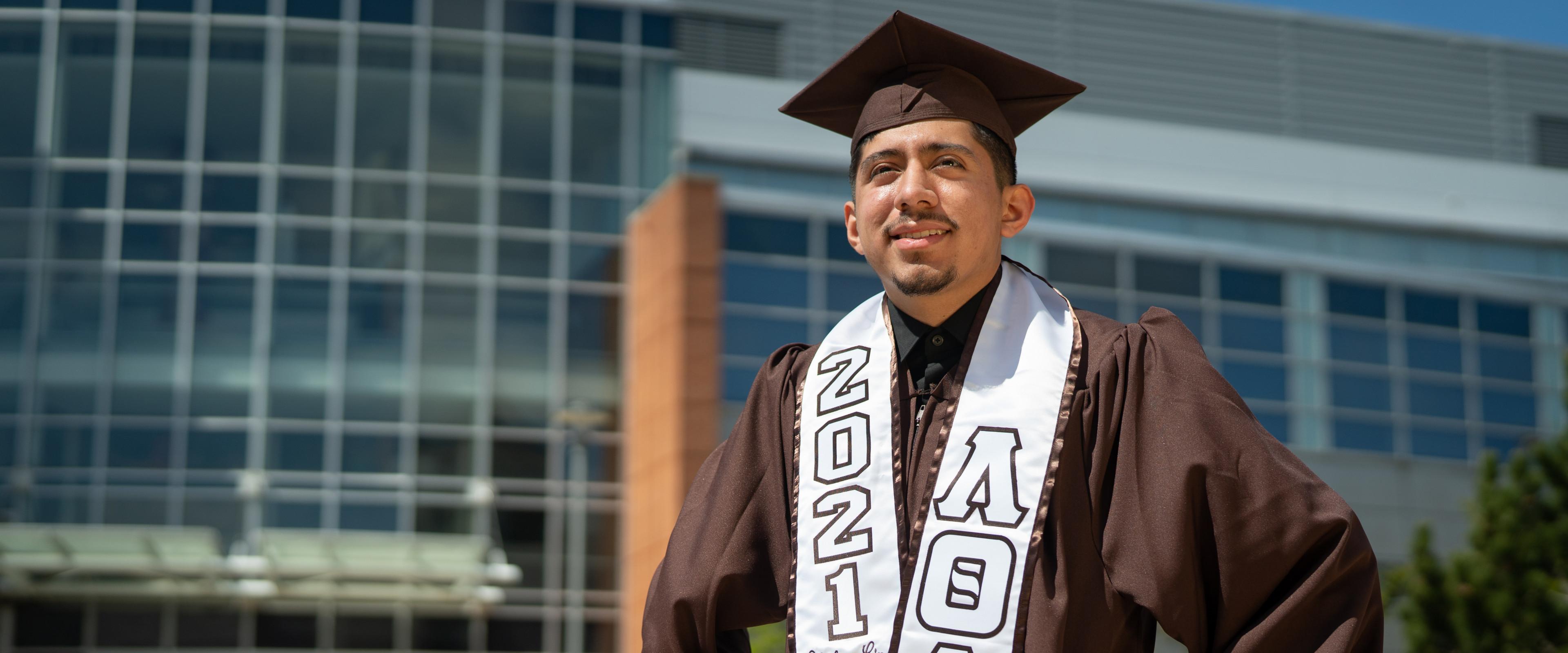 Jovanny Ruiz-Alavez stands in his graduation cap and gown