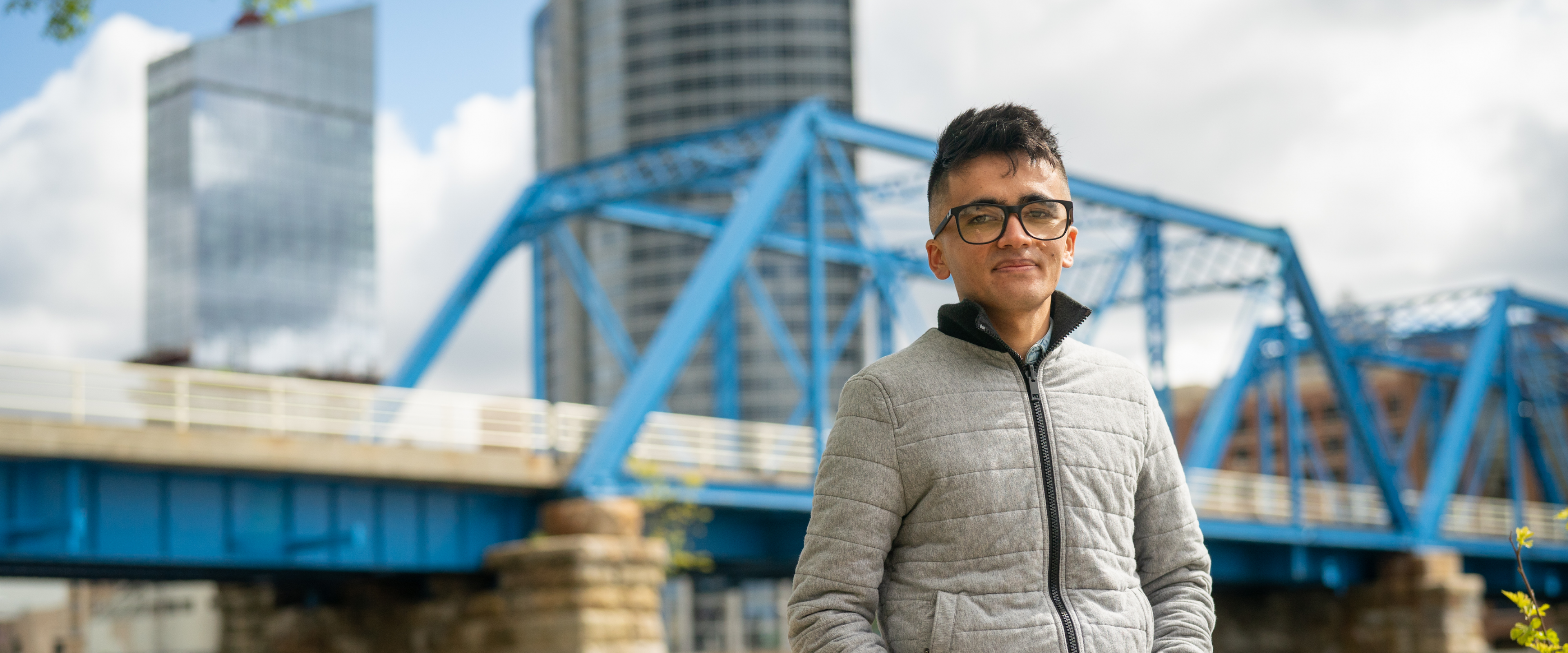 A photo of Zabihullah Najafi with a blue bridge in the background.