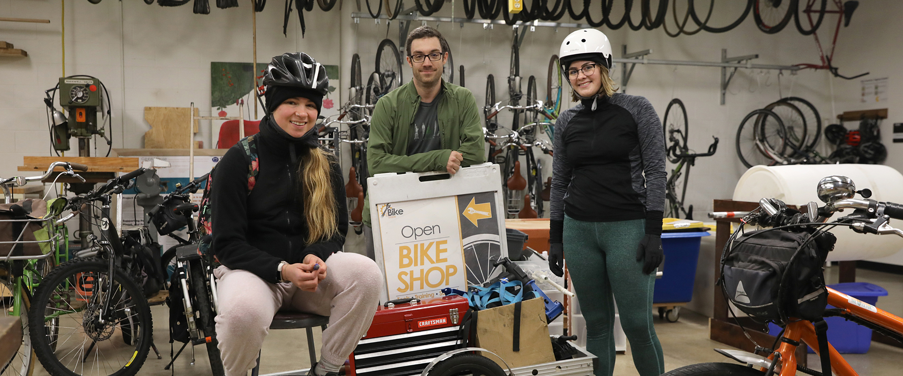 Slideshow image: WMU students in cycling gear pose in the campus bike shop.