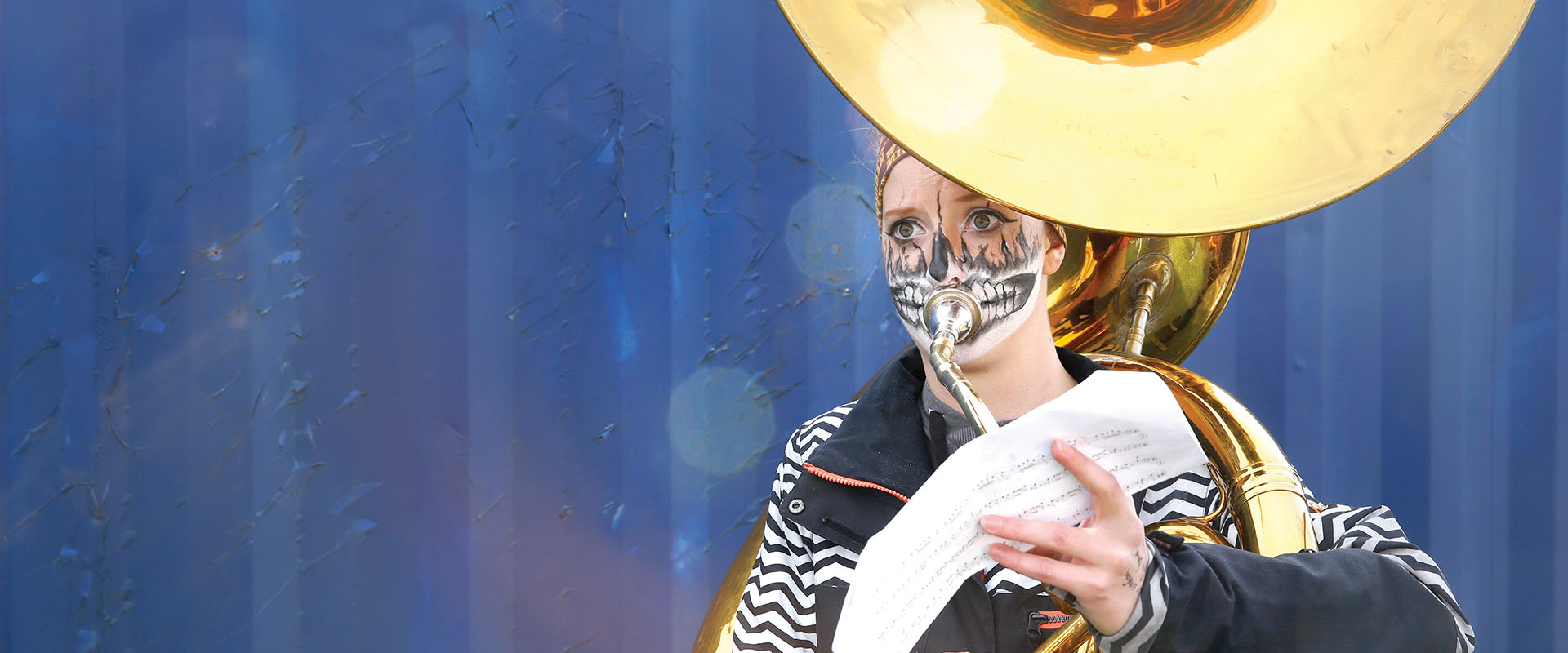 A WMU student with her face painted plays the tuba