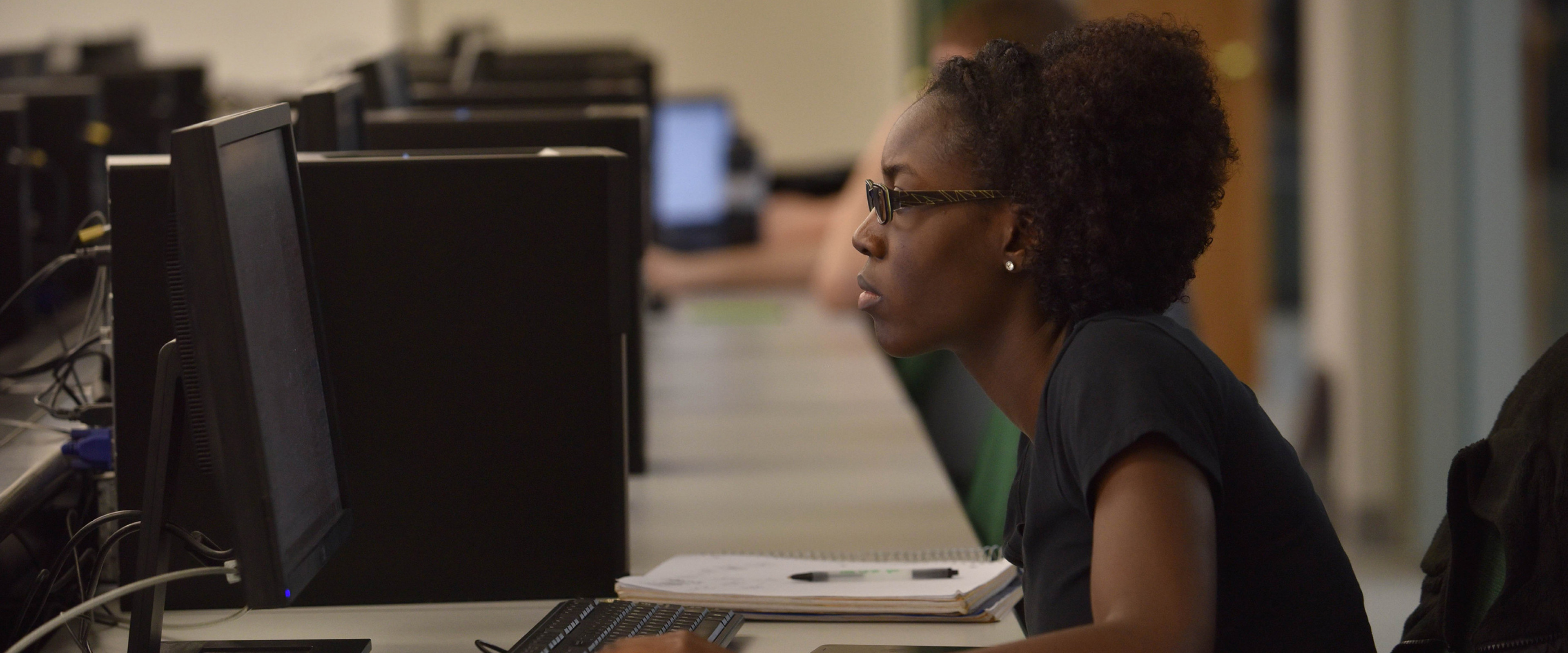 A woman sitting at a computer at the Haworth College of business.