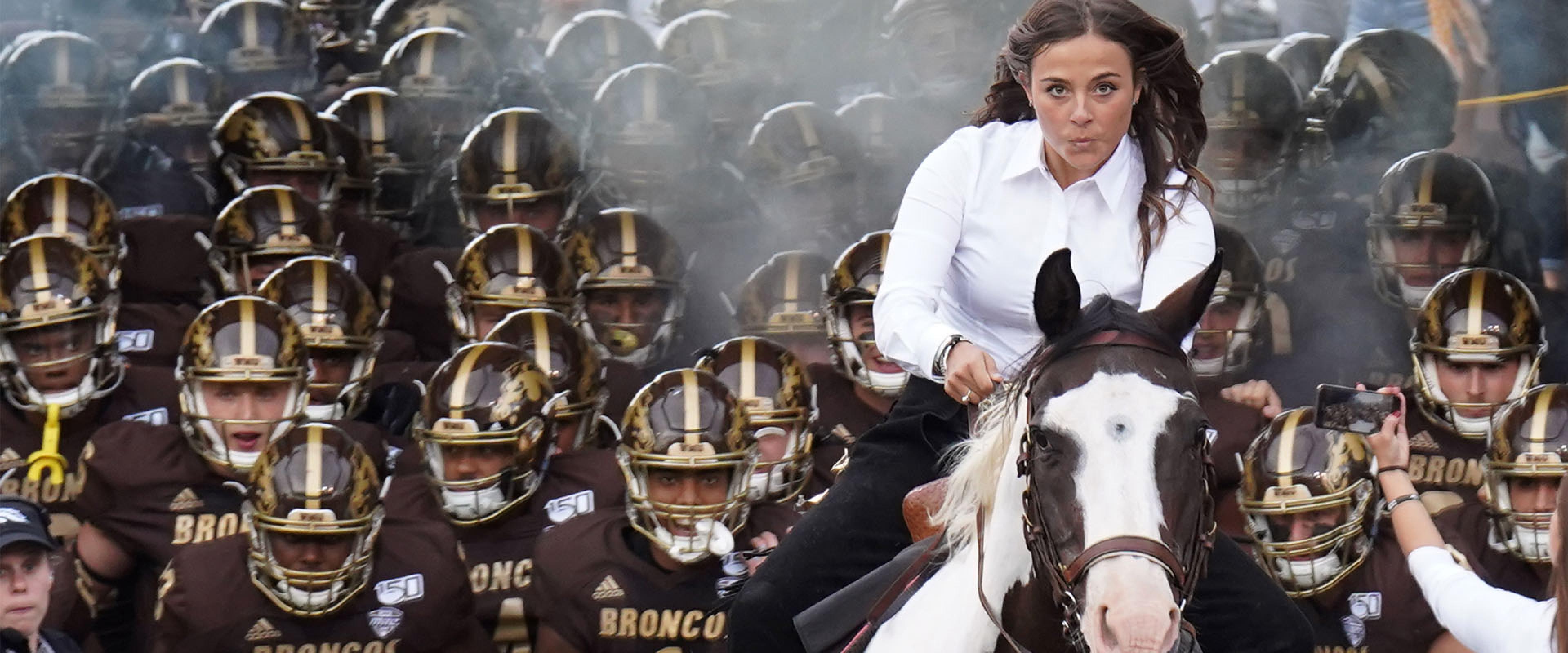 A student on horseback leads the WMU football team onto the field