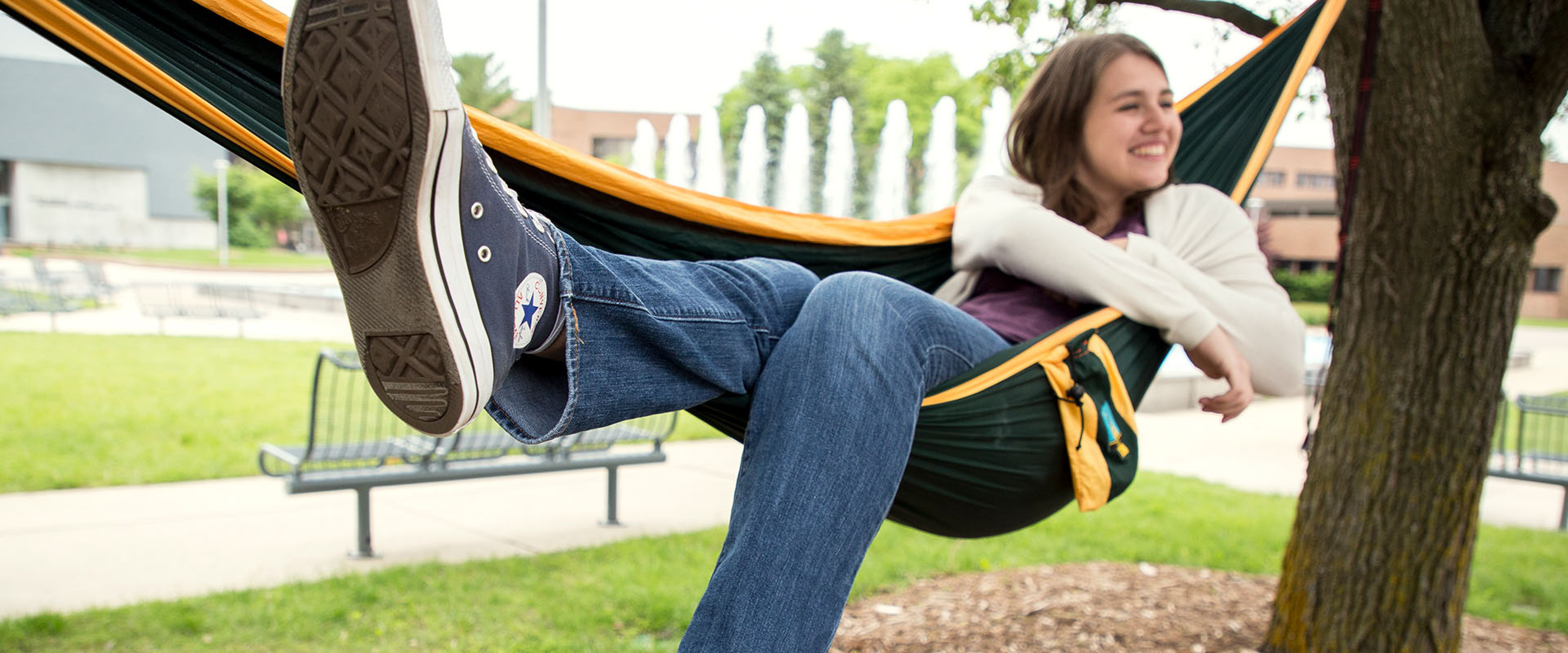 A WMU student relaxes in a hammock in front of the Miller Plaza fountain