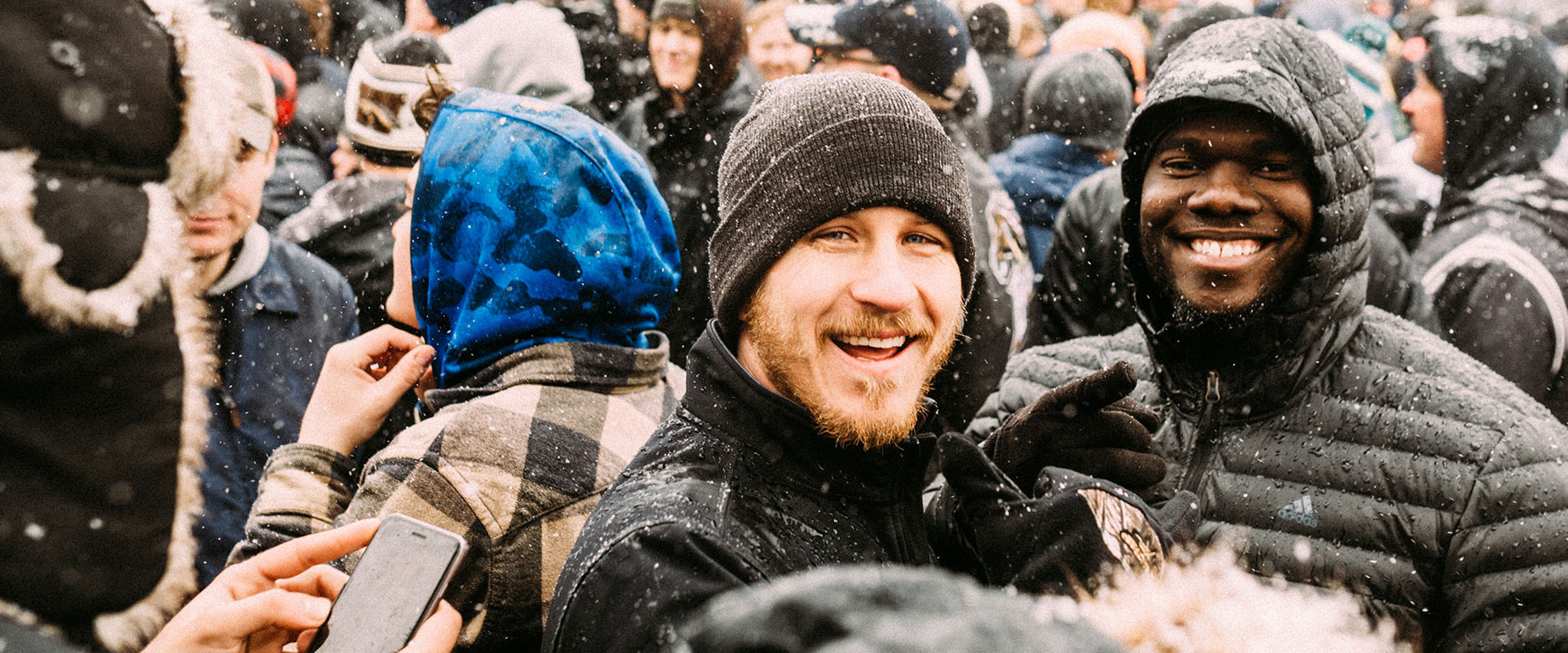 Two WMU students smile amidst a crowd on a snowy day