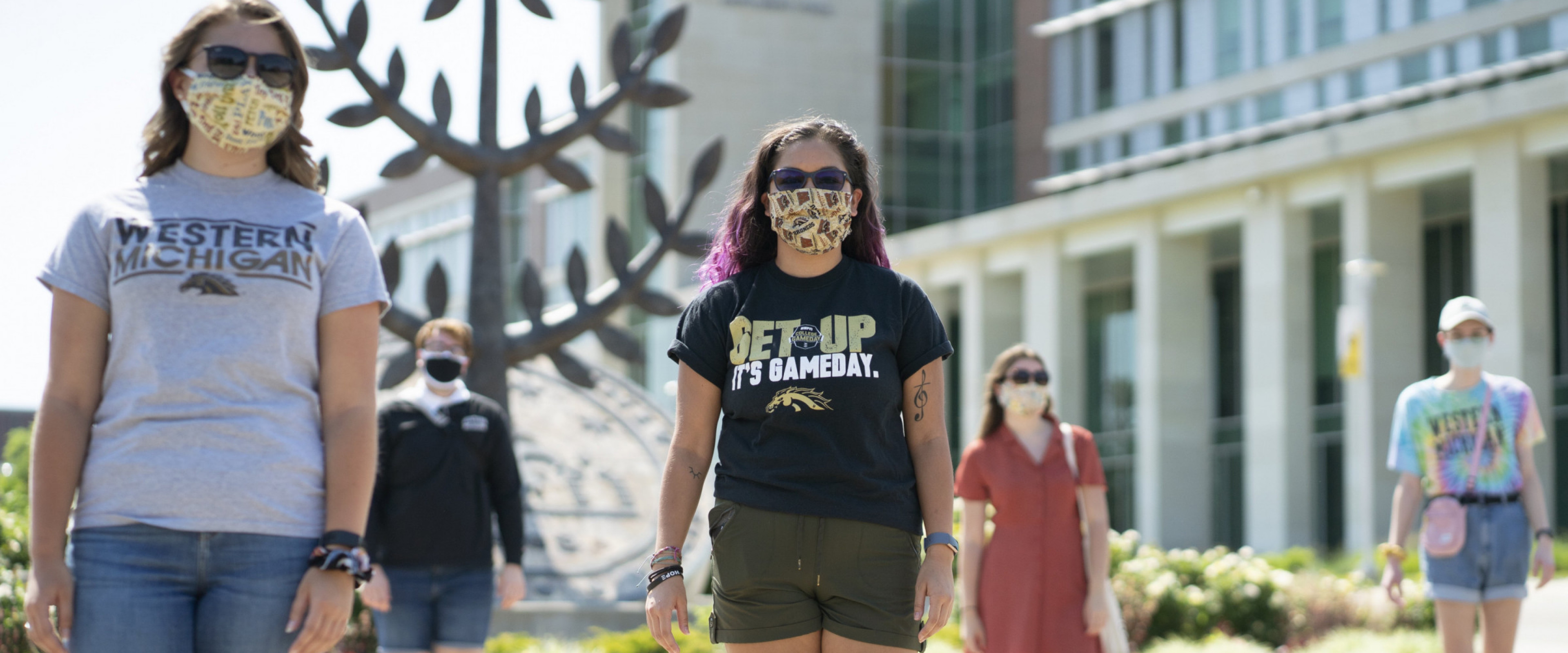 A group of students standing on campus wearing masks.