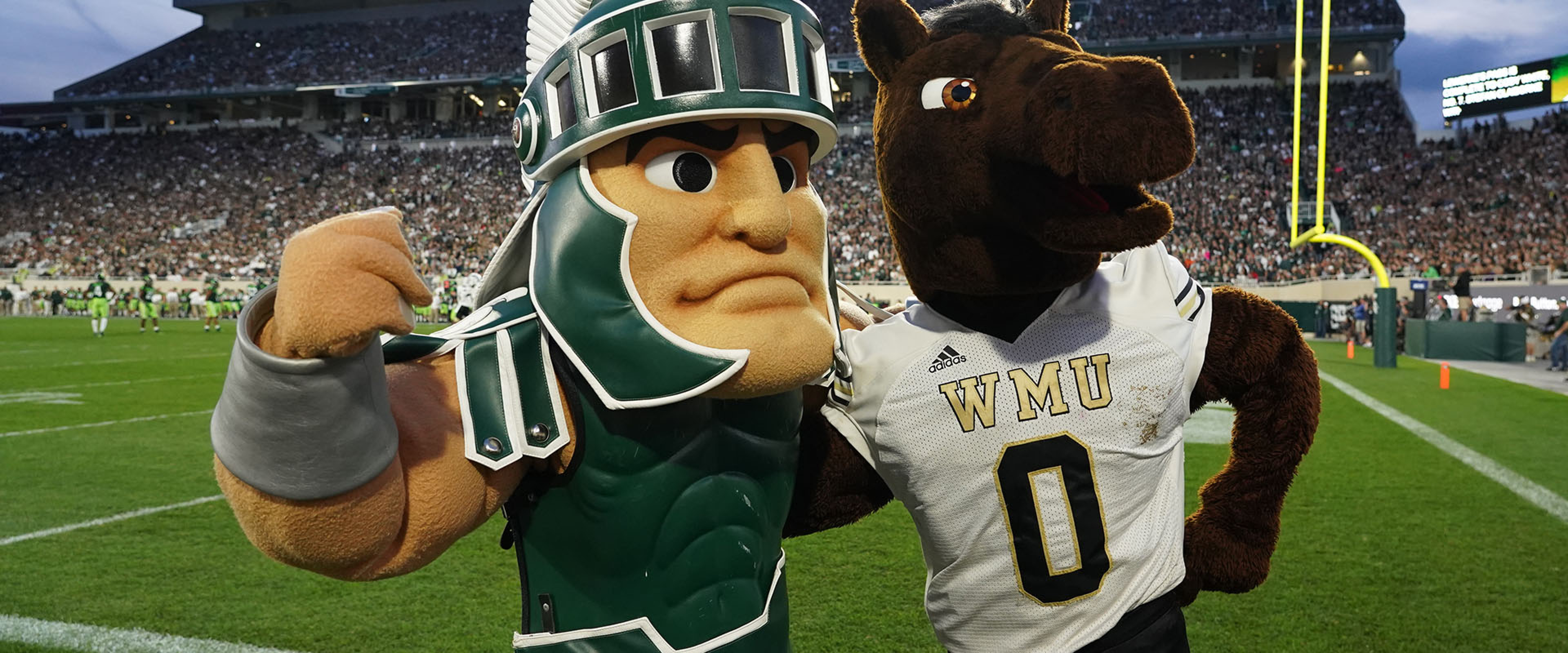 WMU mascot Buster Bronco stands arm-in-arm with MSU mascot Sparty