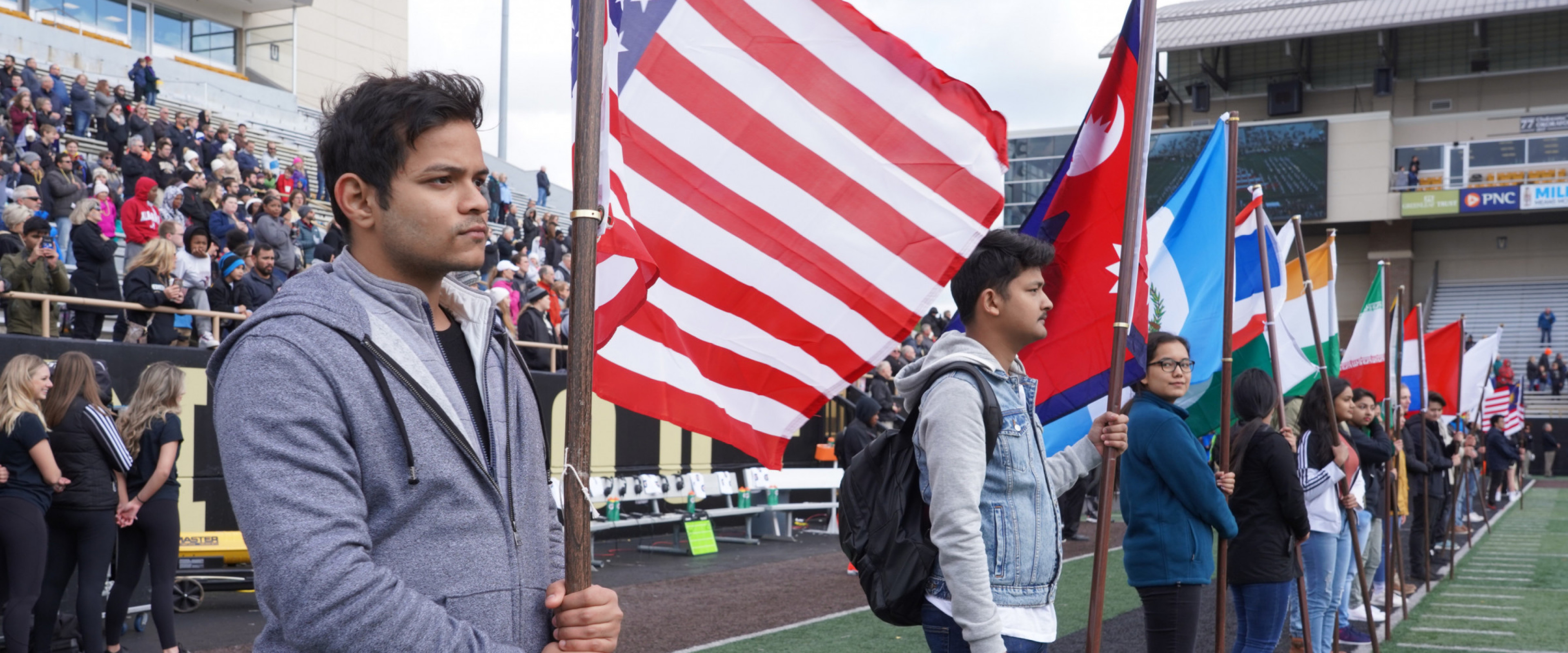 A group of students carries international flags on the field at Waldo Stadium.