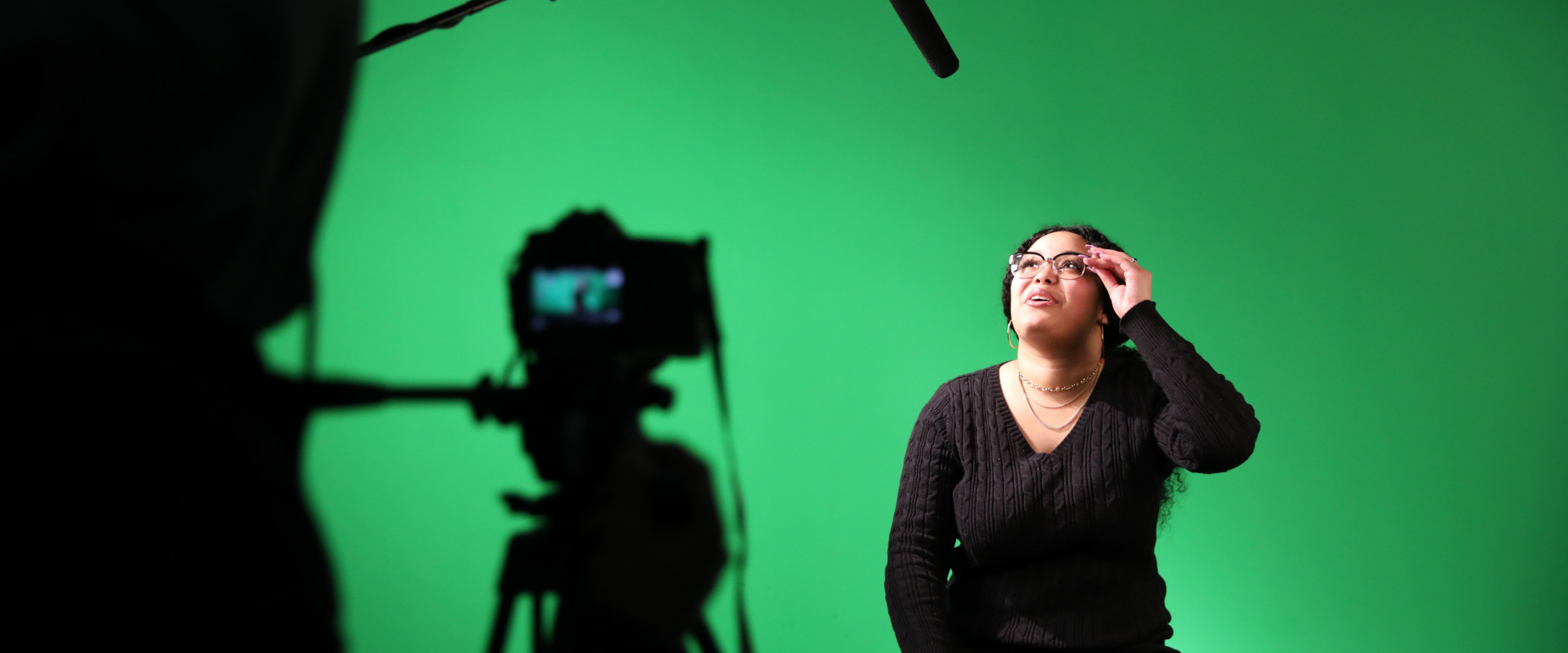 Student sitting behind camera with greenscreen