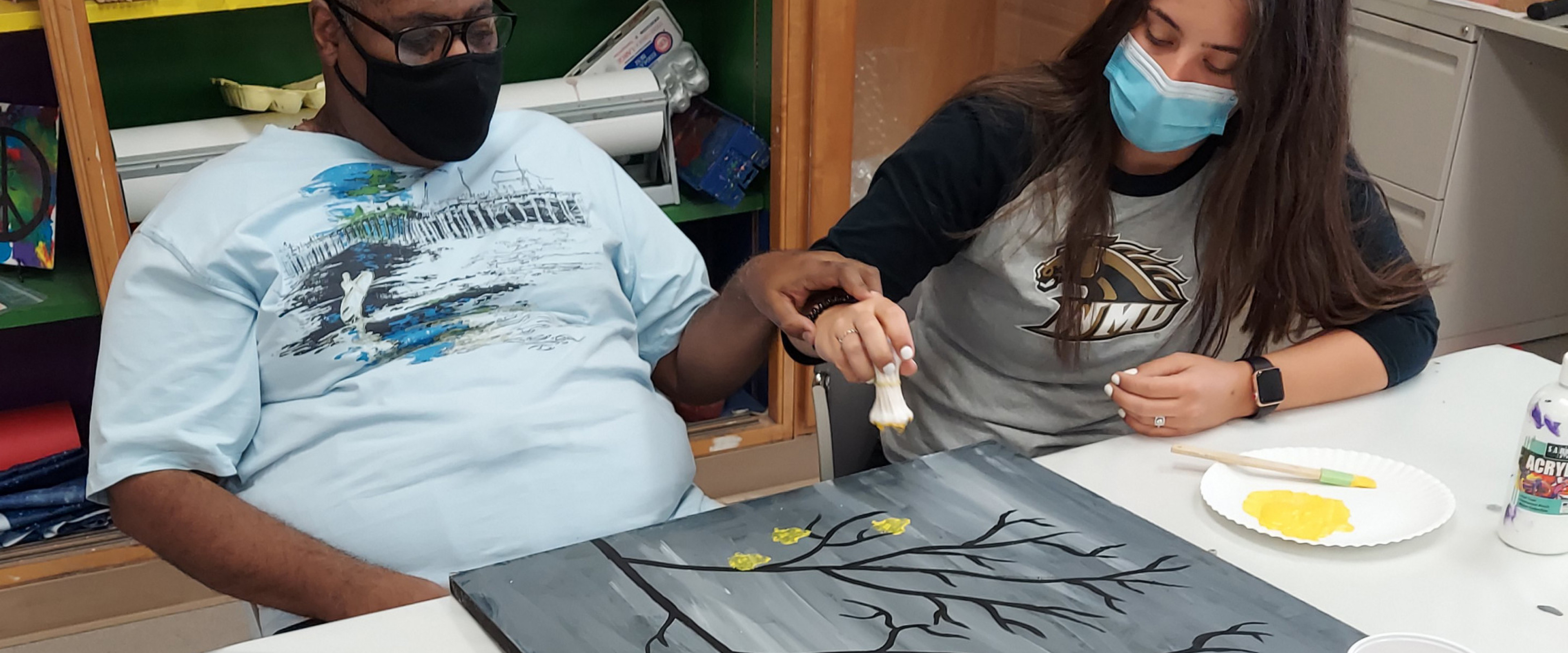 WMU student and participant painting together