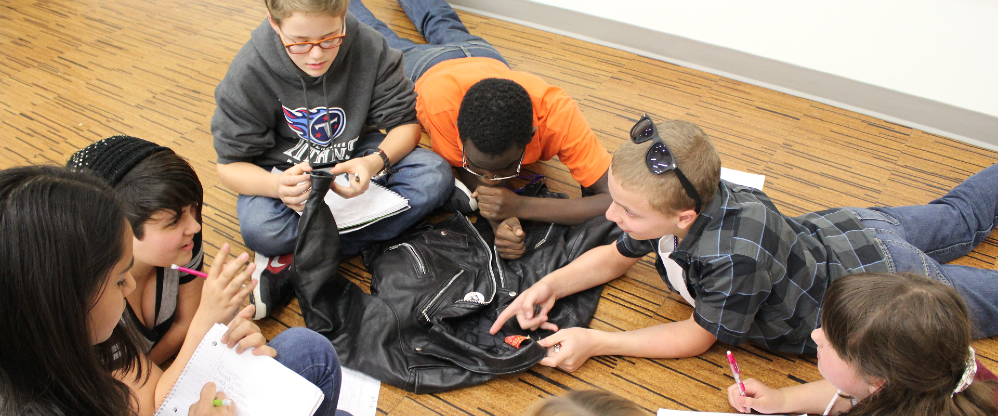 Several students gathered around a jacket discussing their observations.