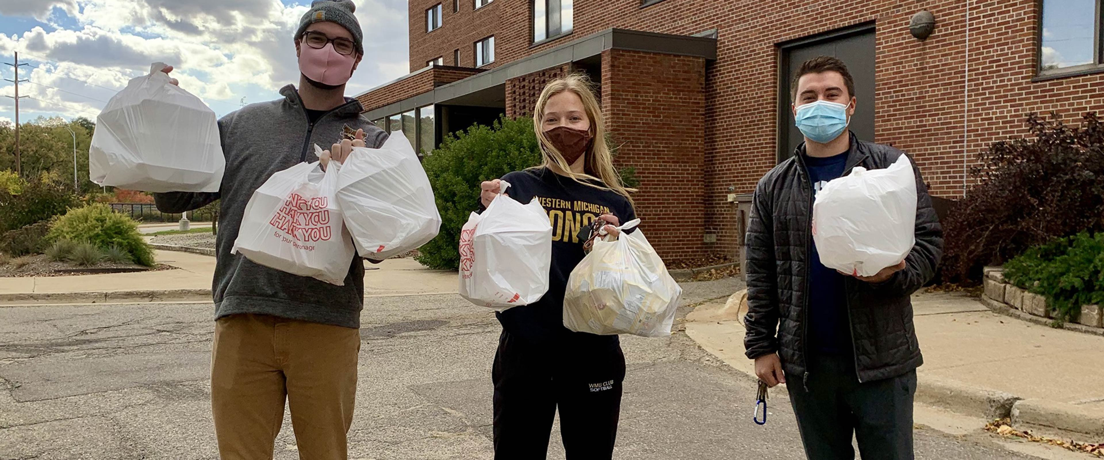 Three students wearing masks holding shopping bags filled with food.
