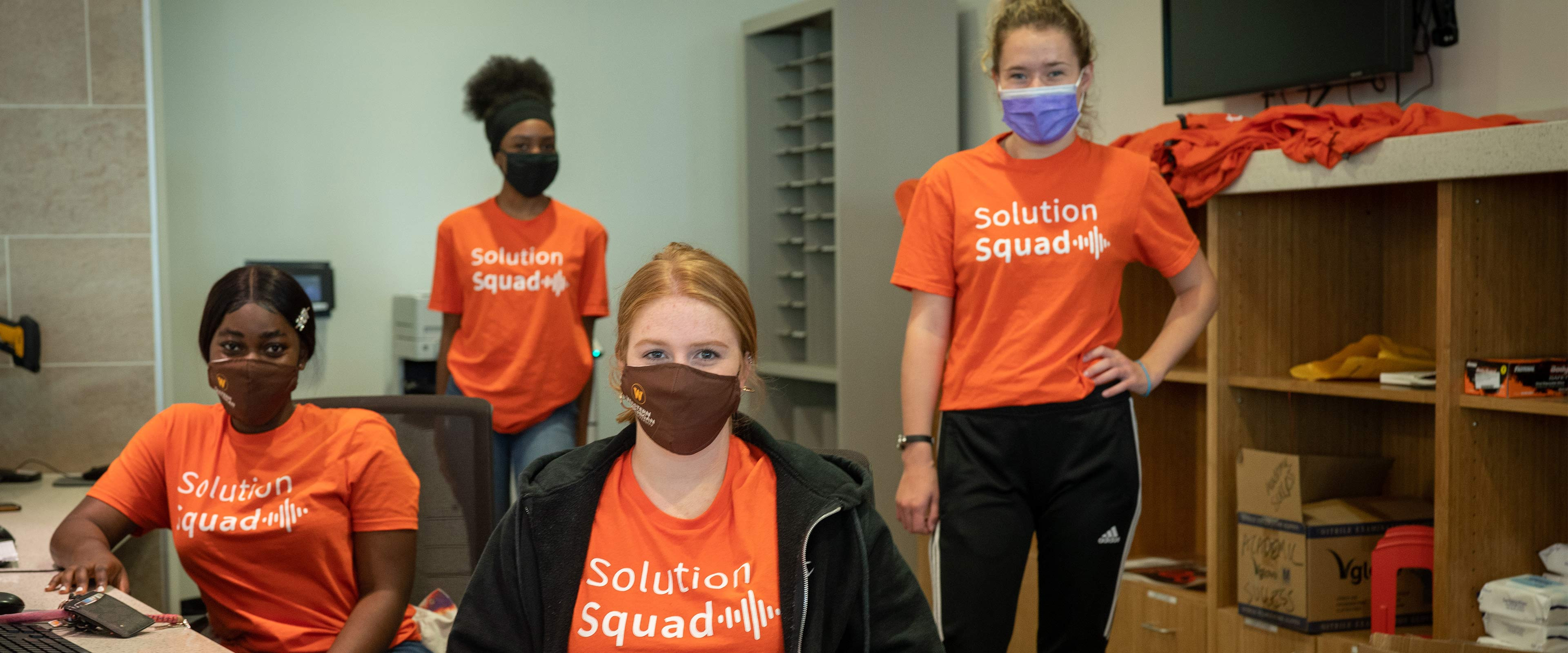 A group of students wearing masks and Solution Squad T-shirts.