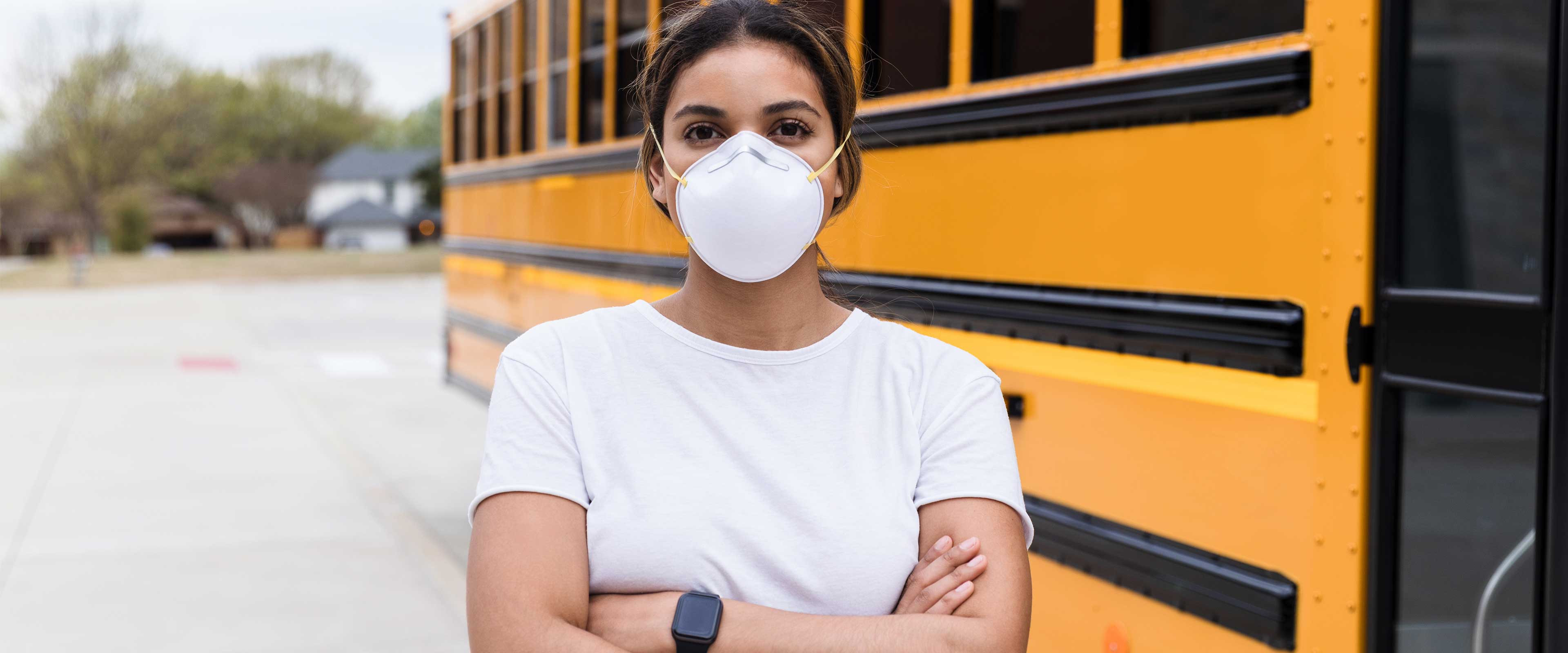 A woman wearing a mask stands next to a school bus.