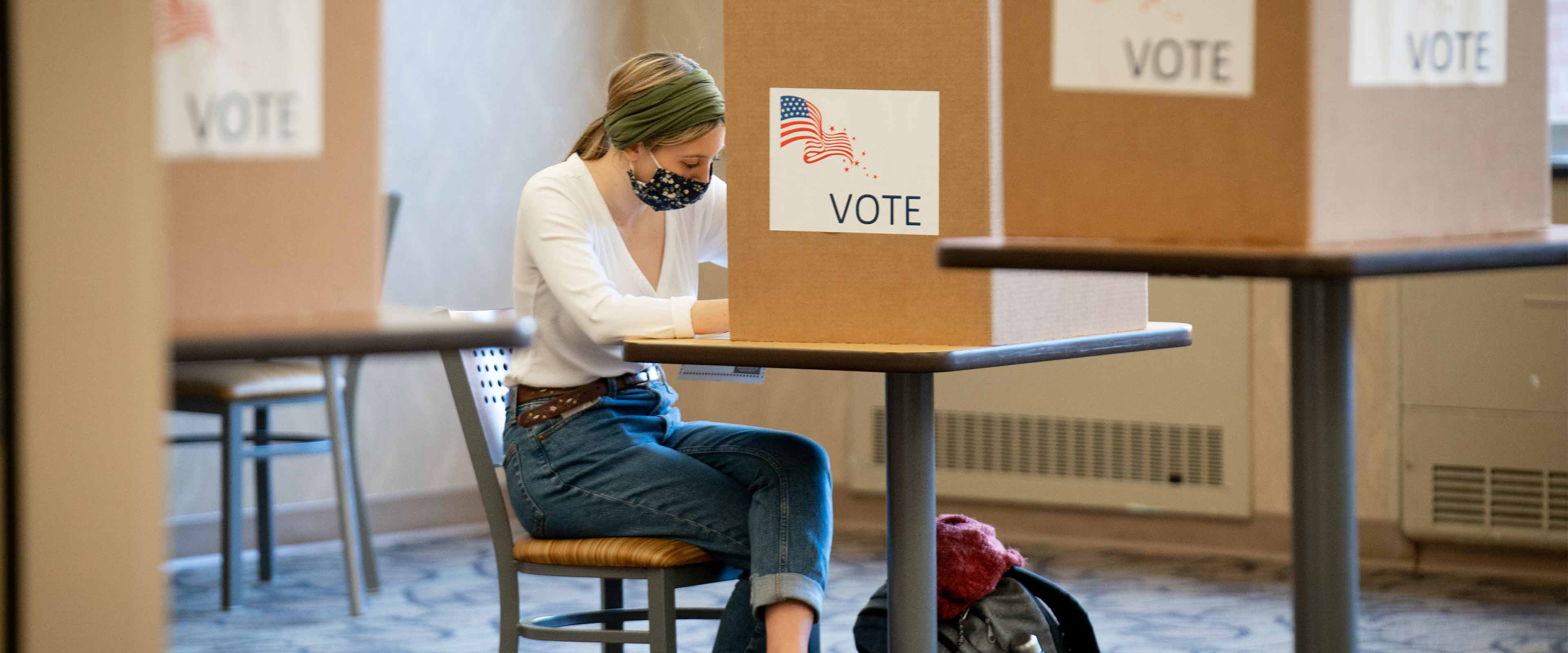 A student fills out her ballot in a new satellite clerk's office on campus.