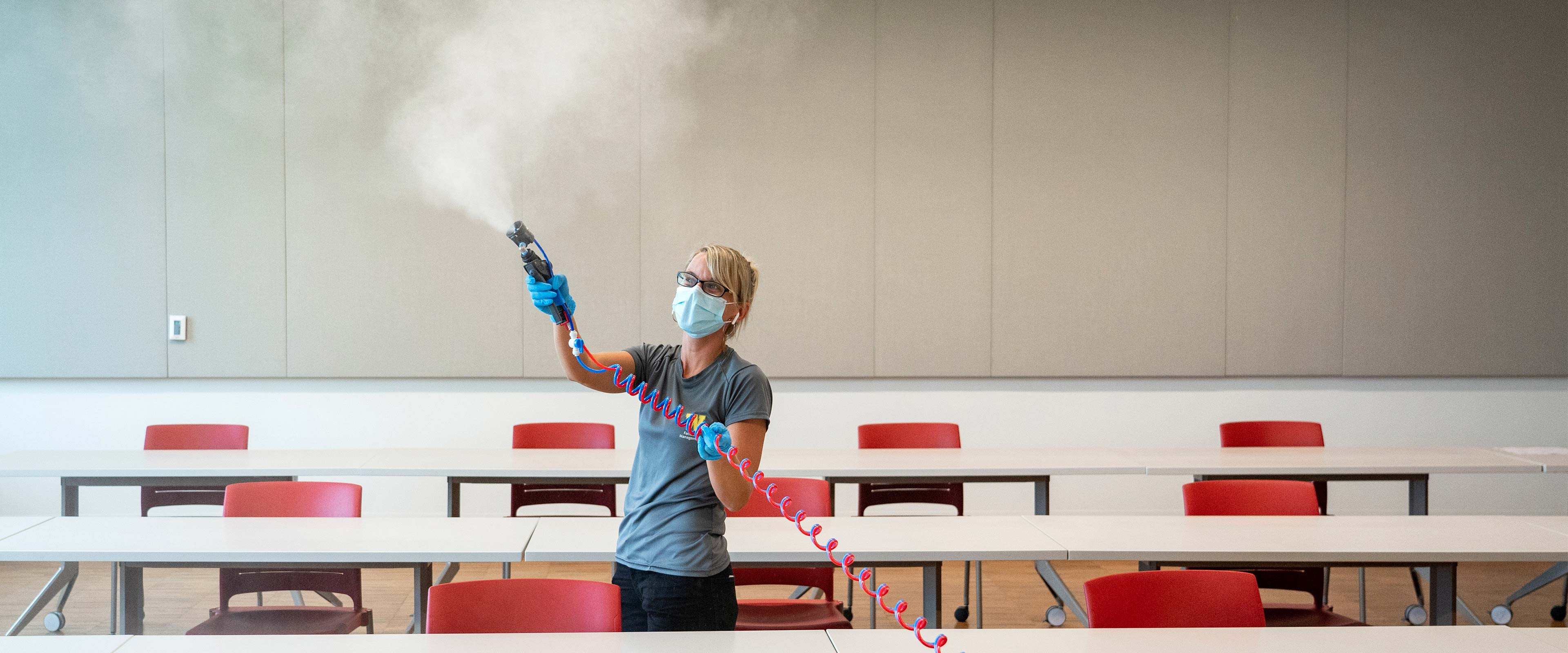 A WMU employee spraying cleaning disinfectant into the air in a classroom.