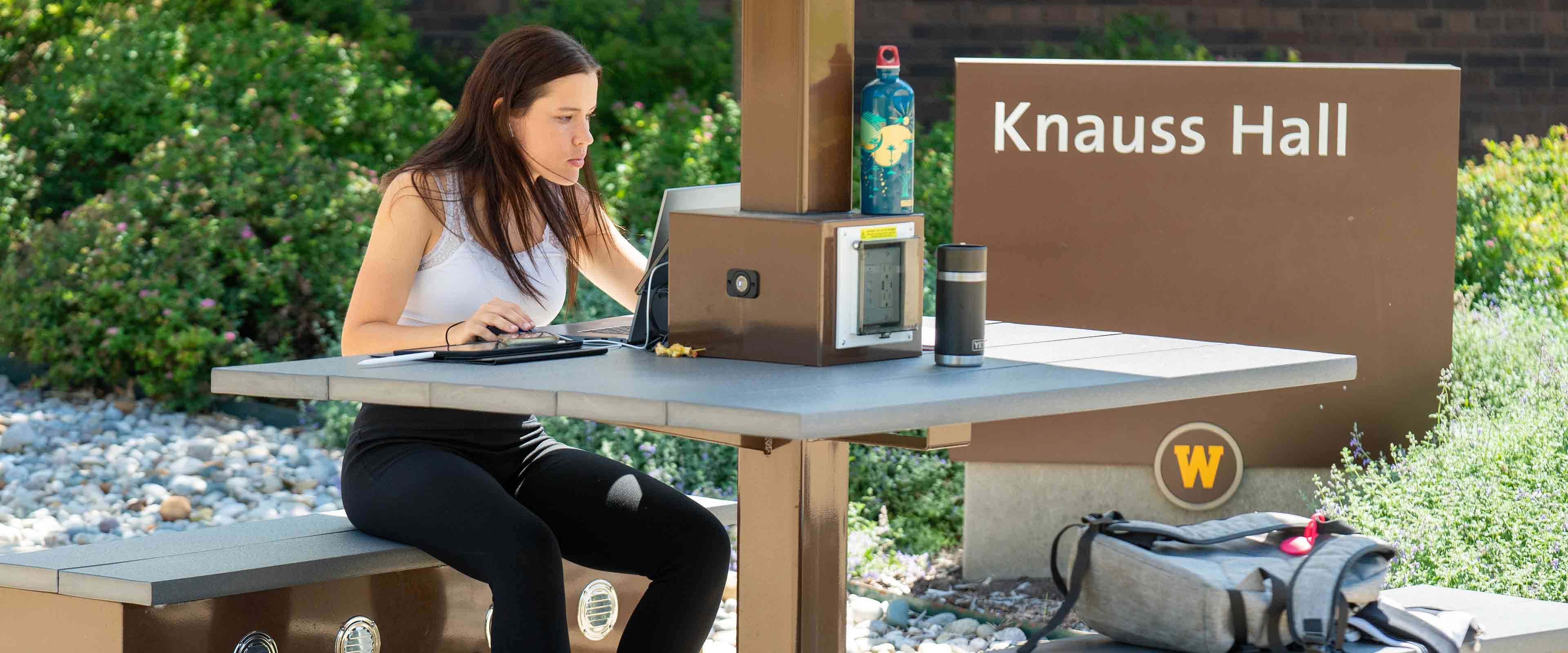 A student studying at a table outside Knauss Hall.