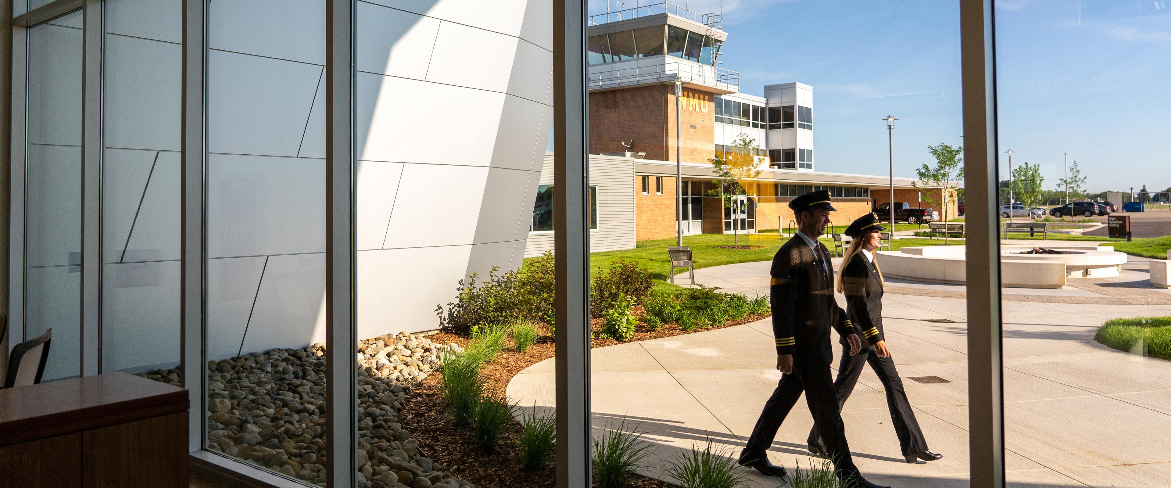 Two pilots walk outside the windows of WMU's Aviation Education Center.