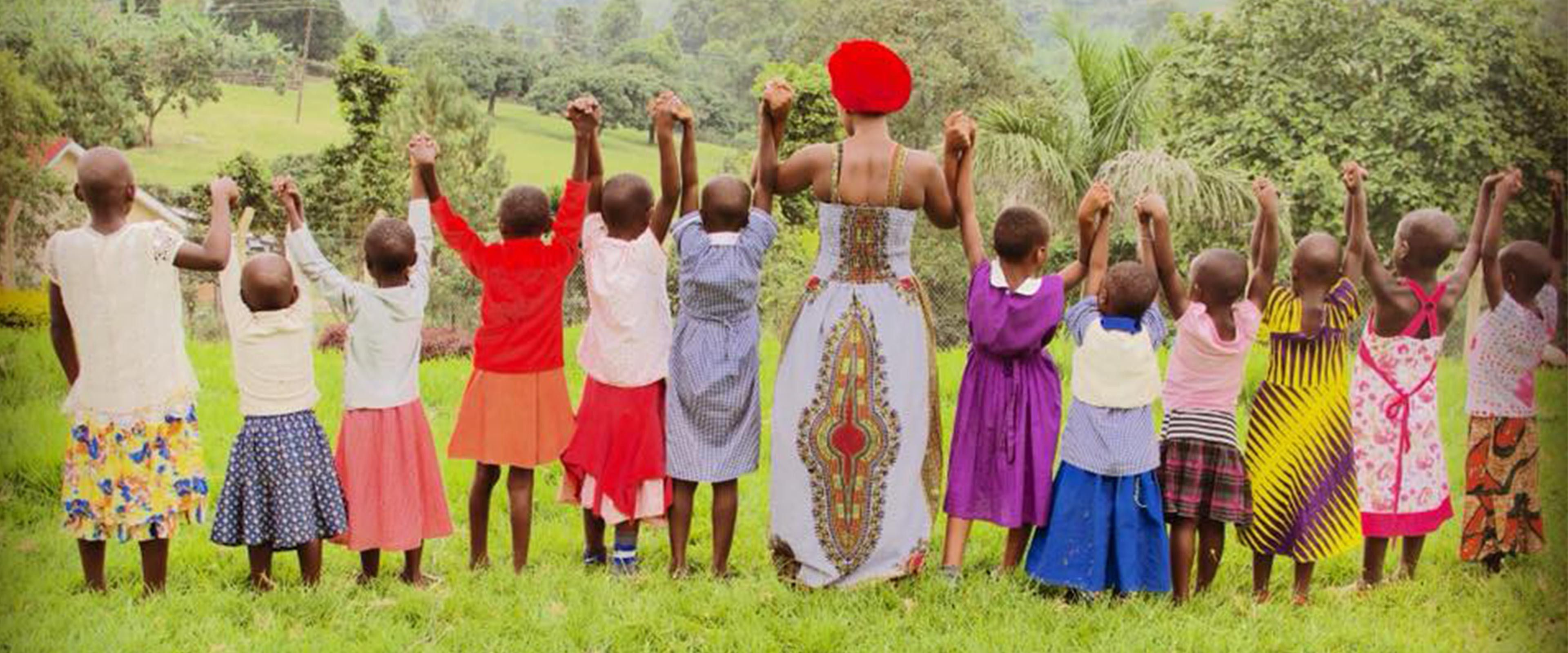 Tabitha Mpamira holding hands with 12 children.