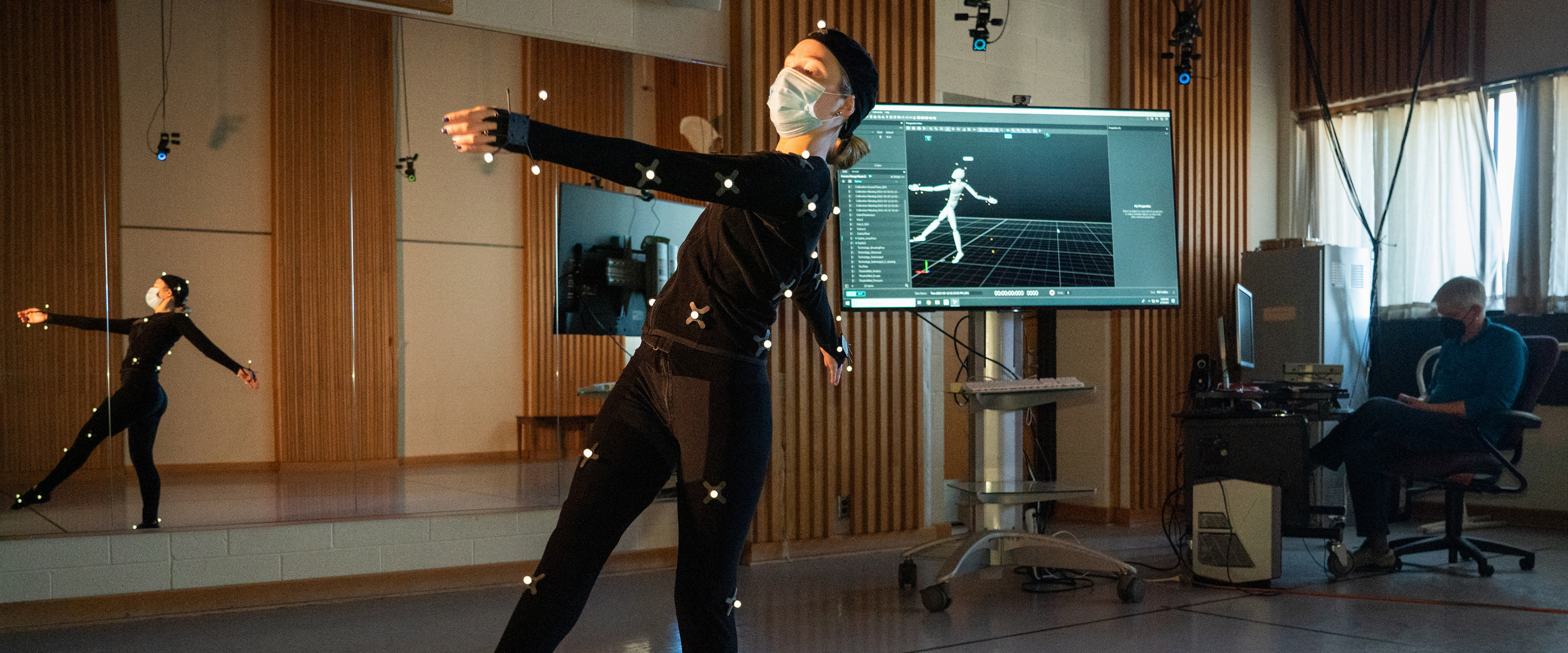 A student wearing a motion capture suit dances in front of a large computer monitor.
