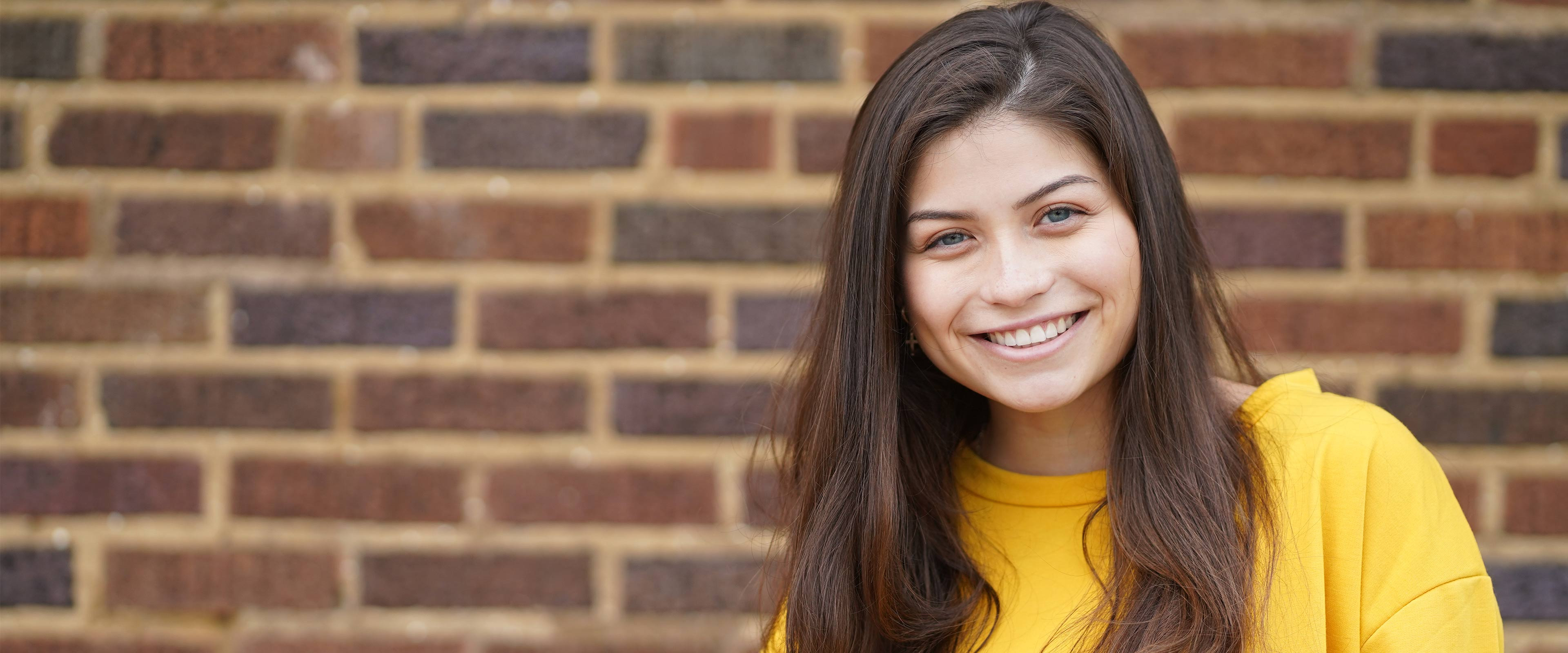 A woman wearing a gold shirt smiles in front of a brick wall.