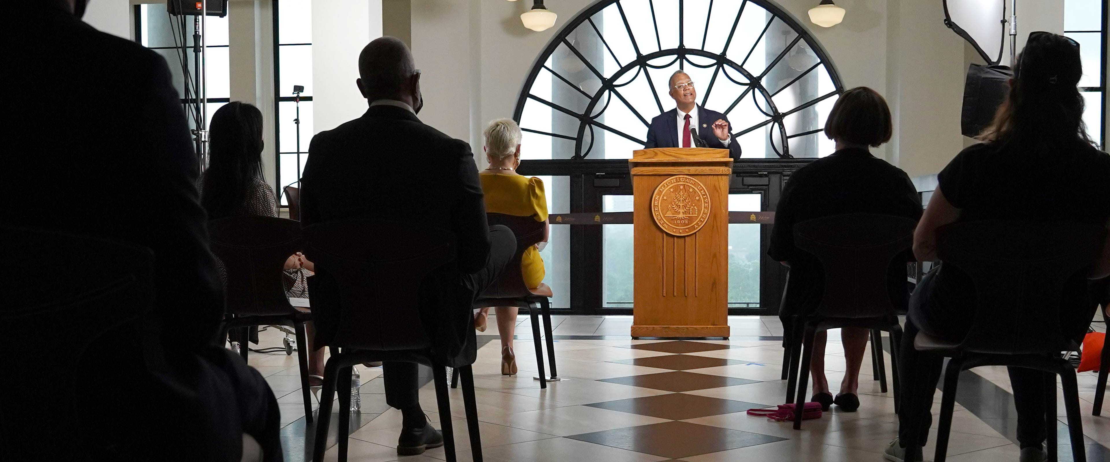 President Montgomery standing at a podium with an audience watching in Heritage Hall.