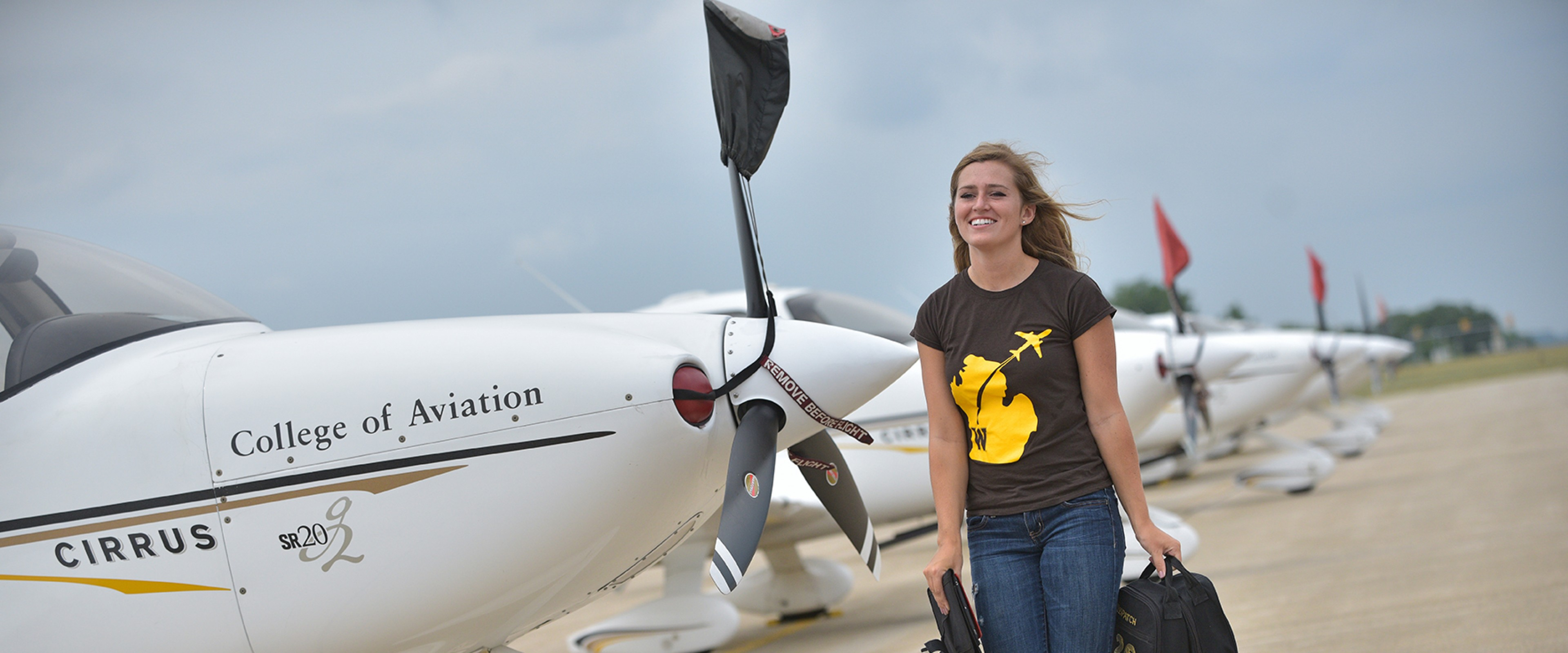 A WMU student pilot walking amongst parked airplanes