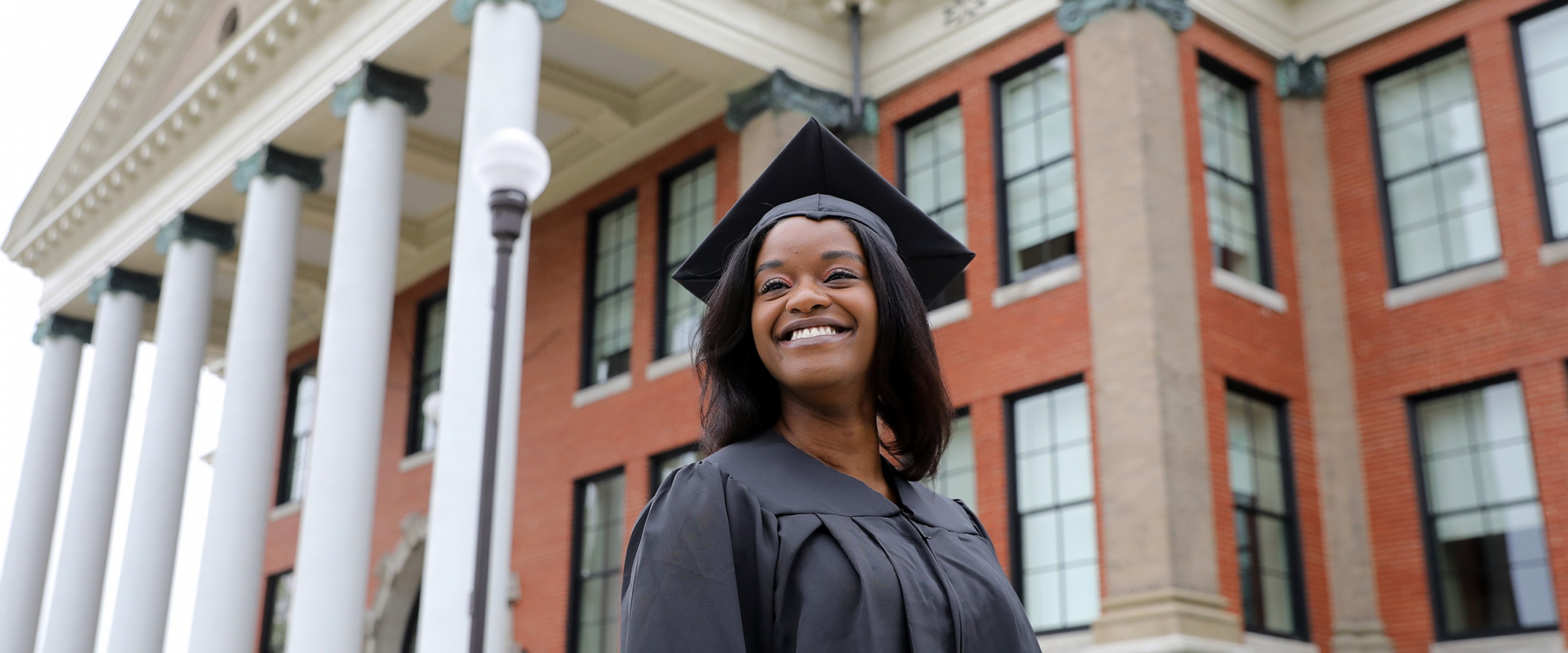 A smiling WMU graduate wearing her cap and gown
