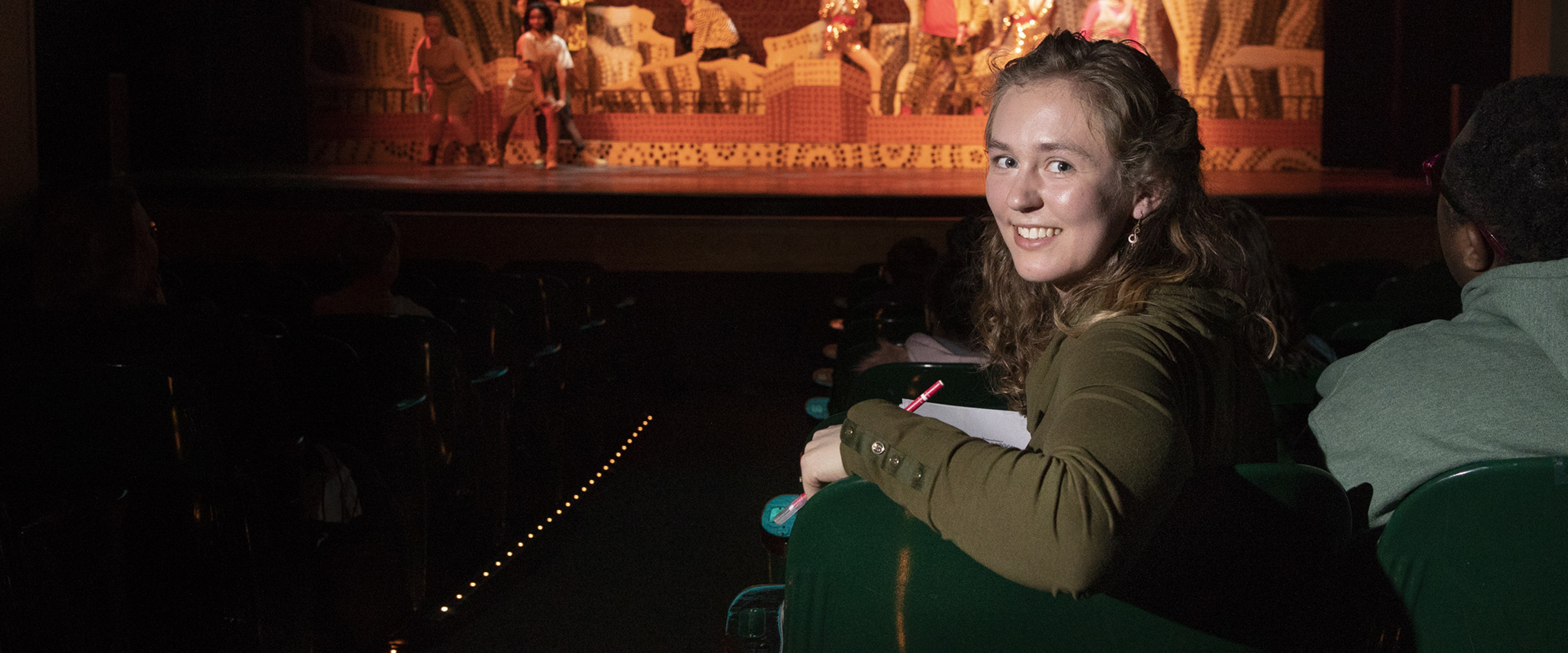 WMU student Abby Tongue sits in a theatre seat as a play is performed onstage