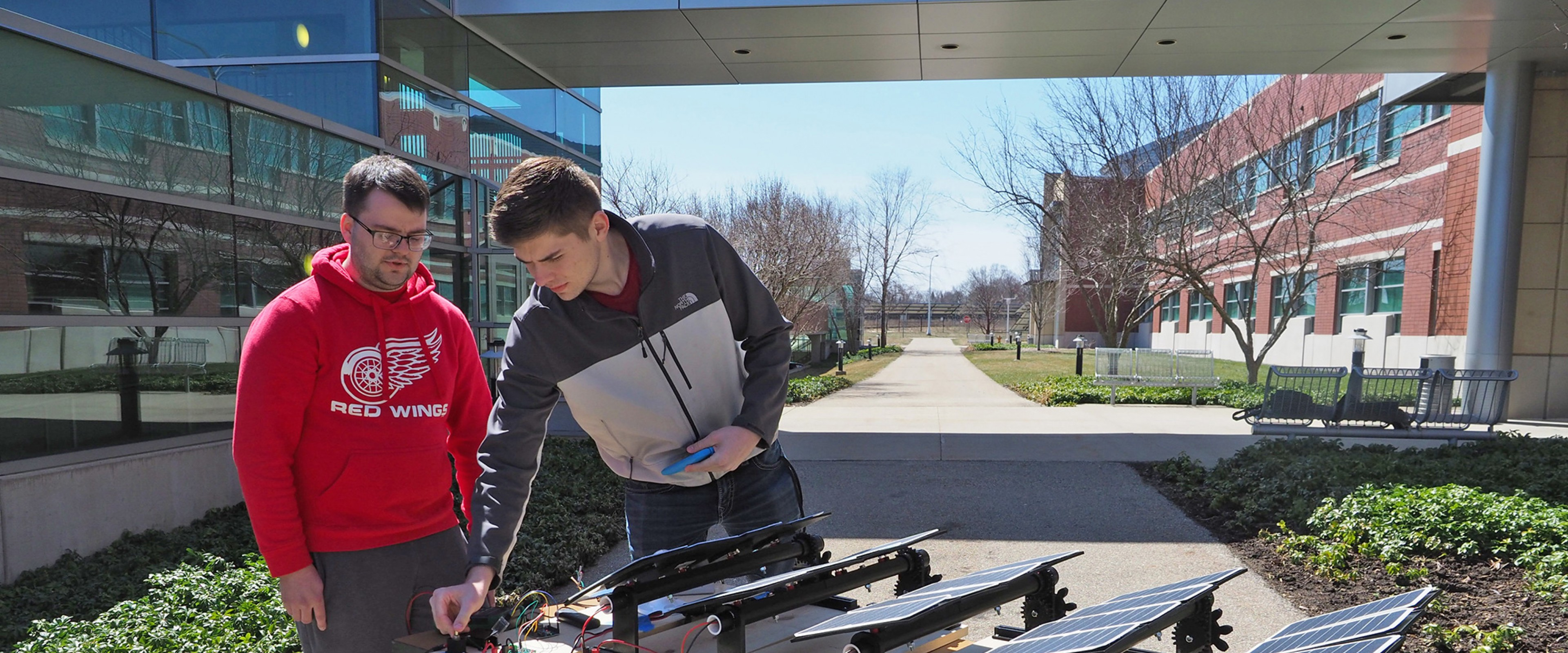 A pair of WMU students work on solar panels in front of Haenicke Hall