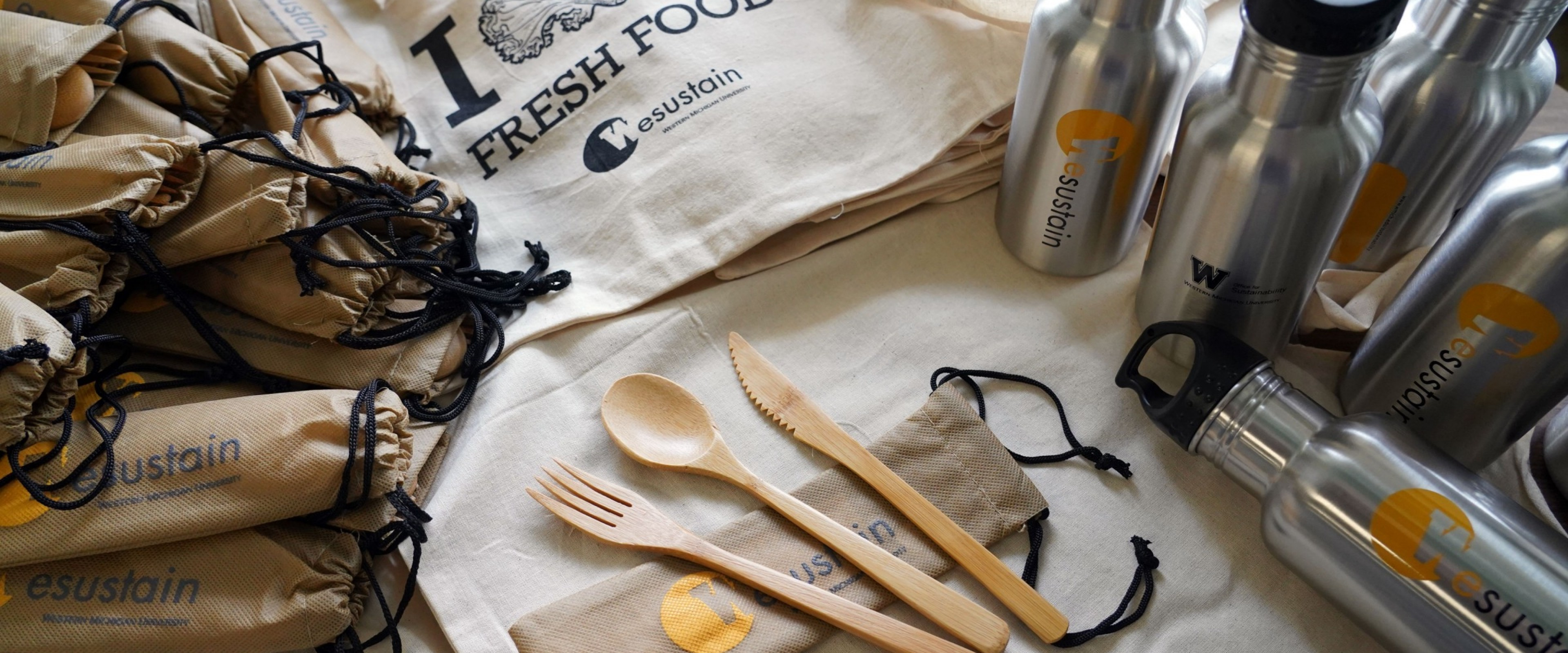 A recyclable bag is the backdrop for bamboo eating utensils and a metal water bottle