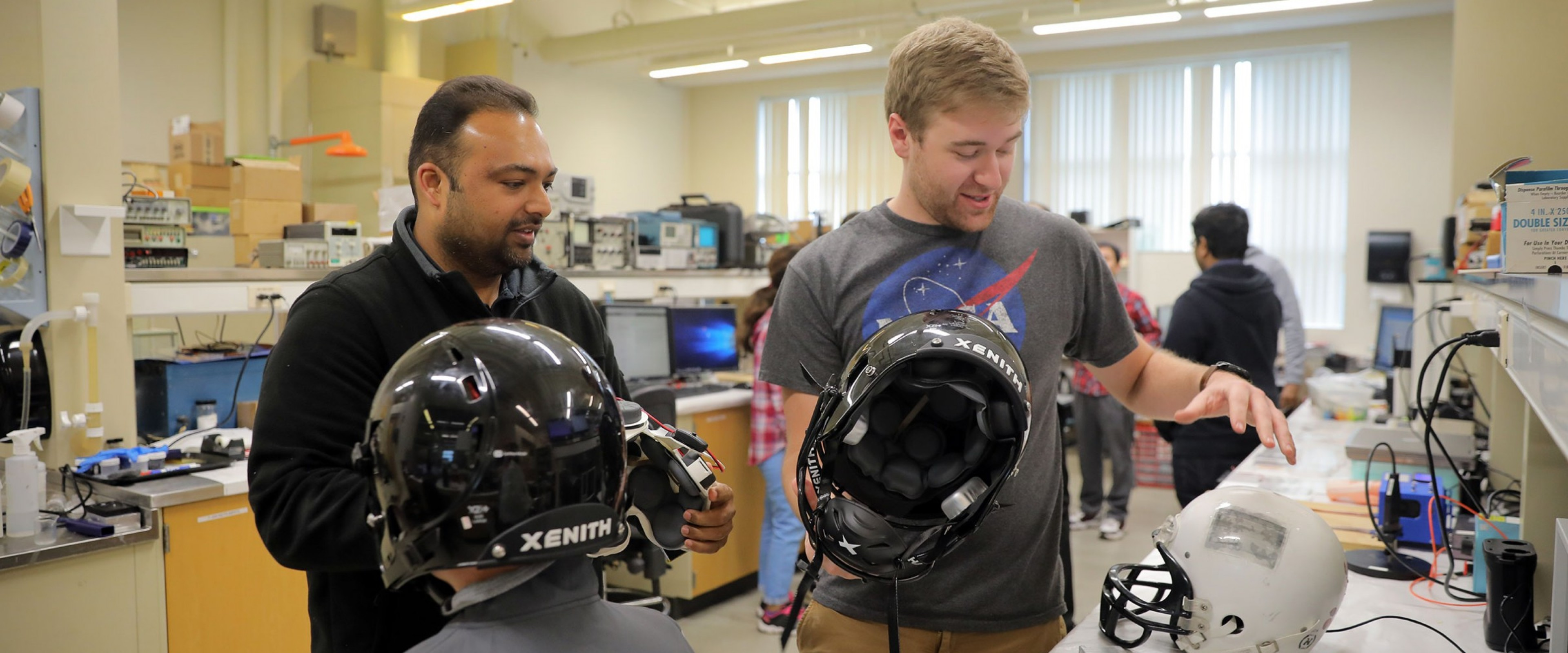 A WMU student and professor work together discussing the safety and design of the helmets they are holding