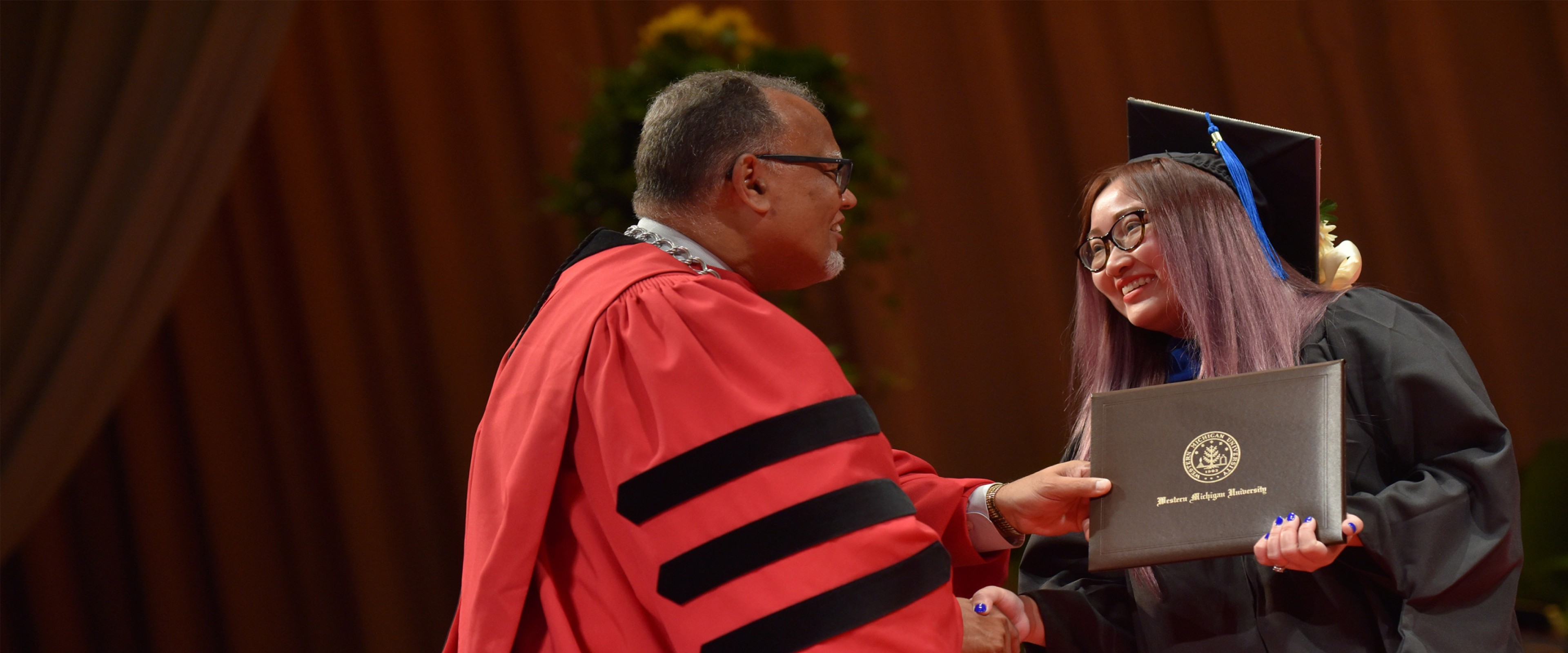 president montgomery shakes the hand of a graduate on stage