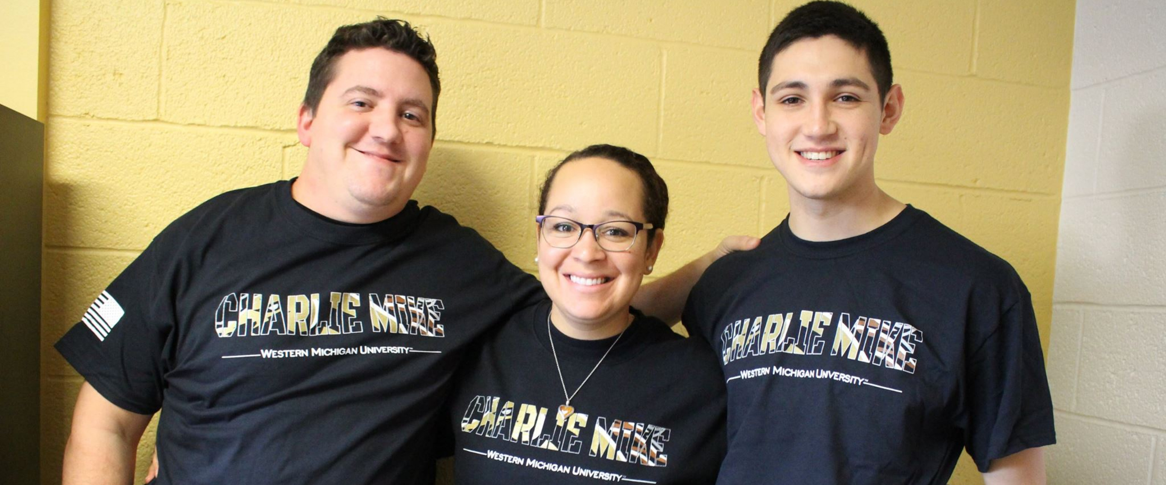 """Three smiling students wearing Charlie Mike t-shirts, WMU's first Universitywide """"unit"""" t-shirt for military students"""