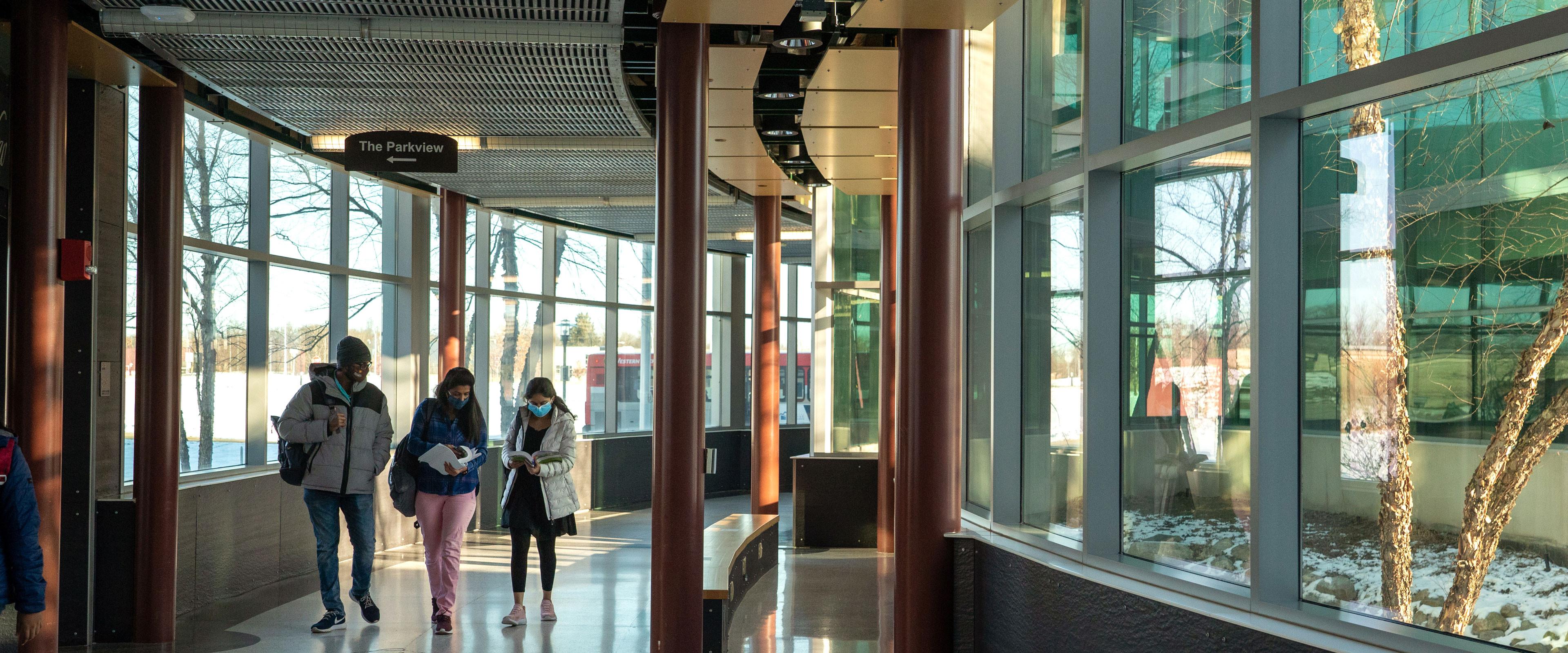 Three students walking in Floyd Hall.