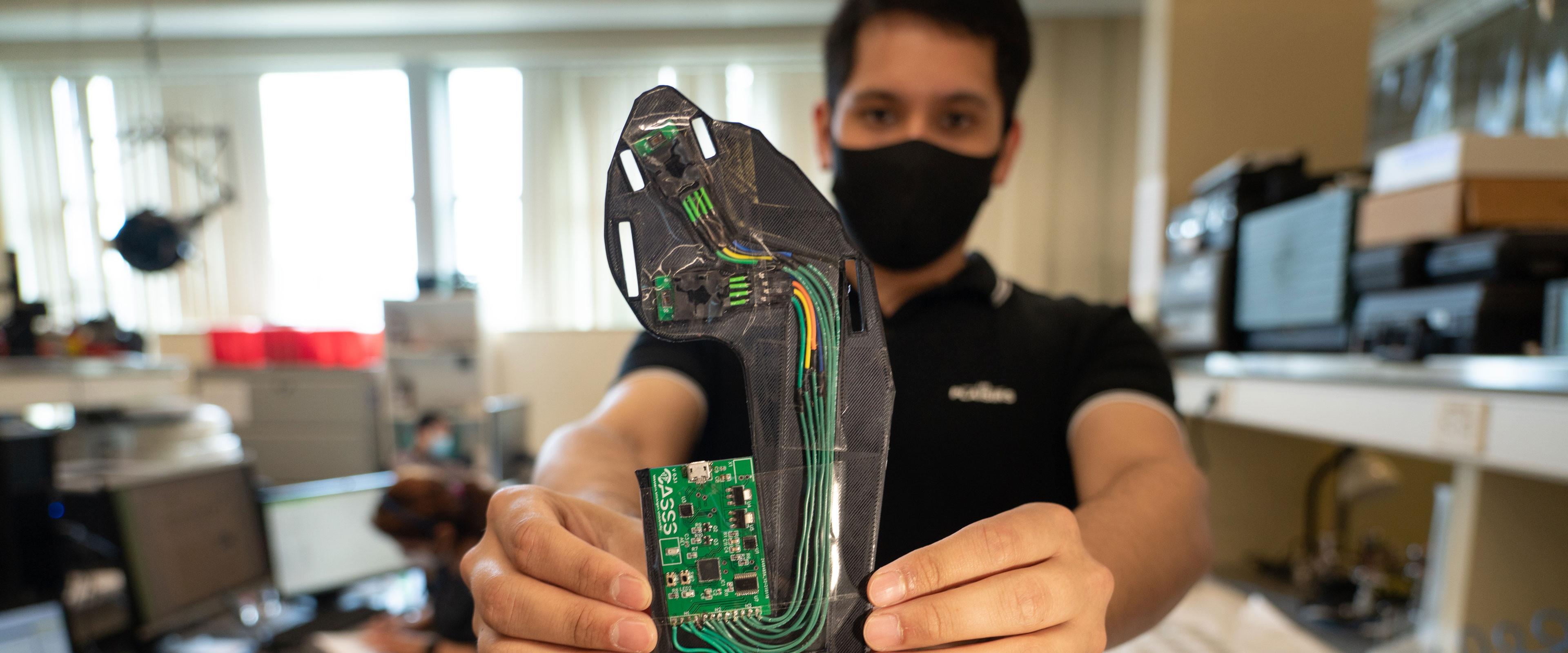 Man holding sensor for diabetic boot.