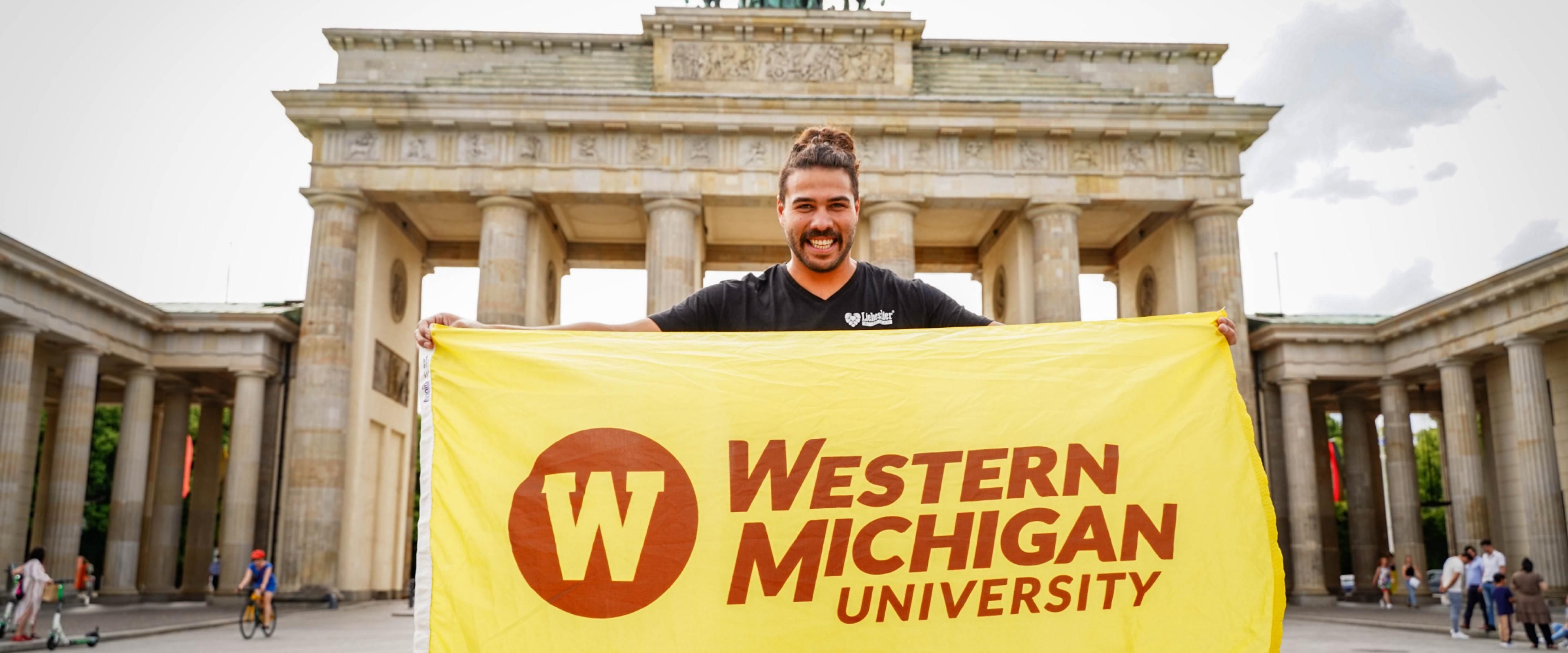 Alumnus holding W flag in Germany