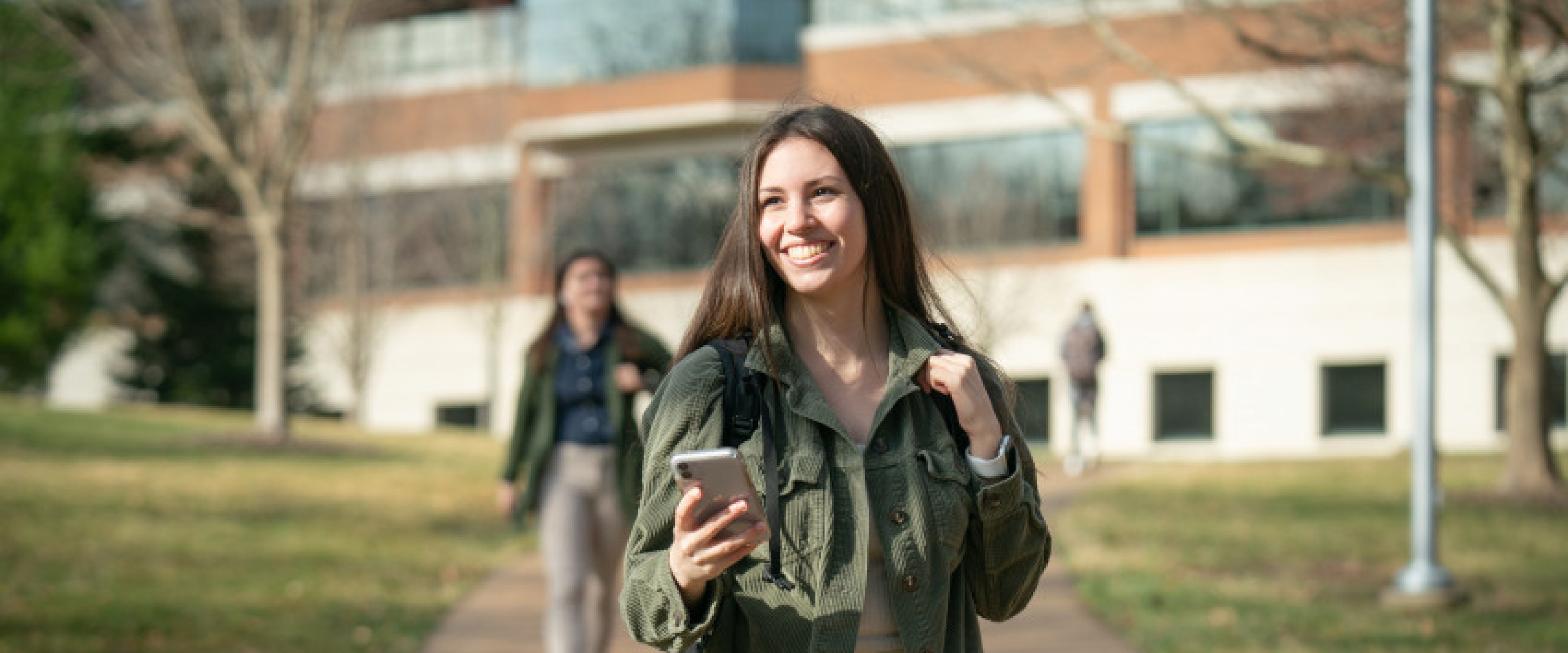 Student walking outside Schneider Hall wearing a backpack and smiling