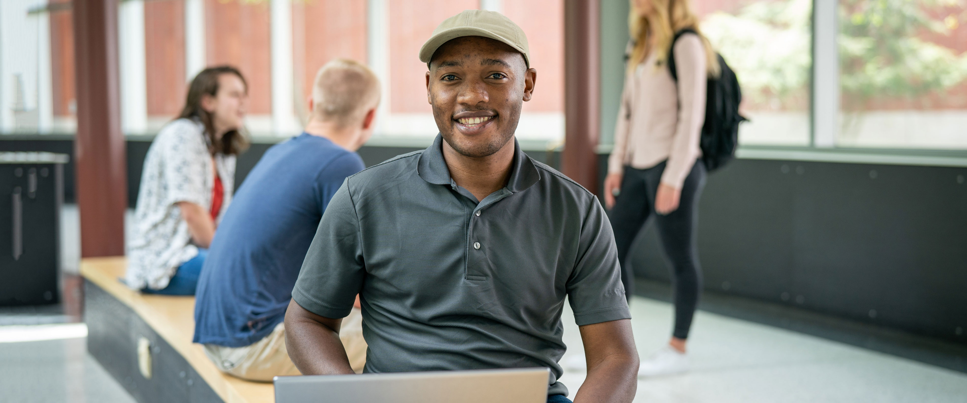 Smiling student sitting in Floyd Hall with laptop