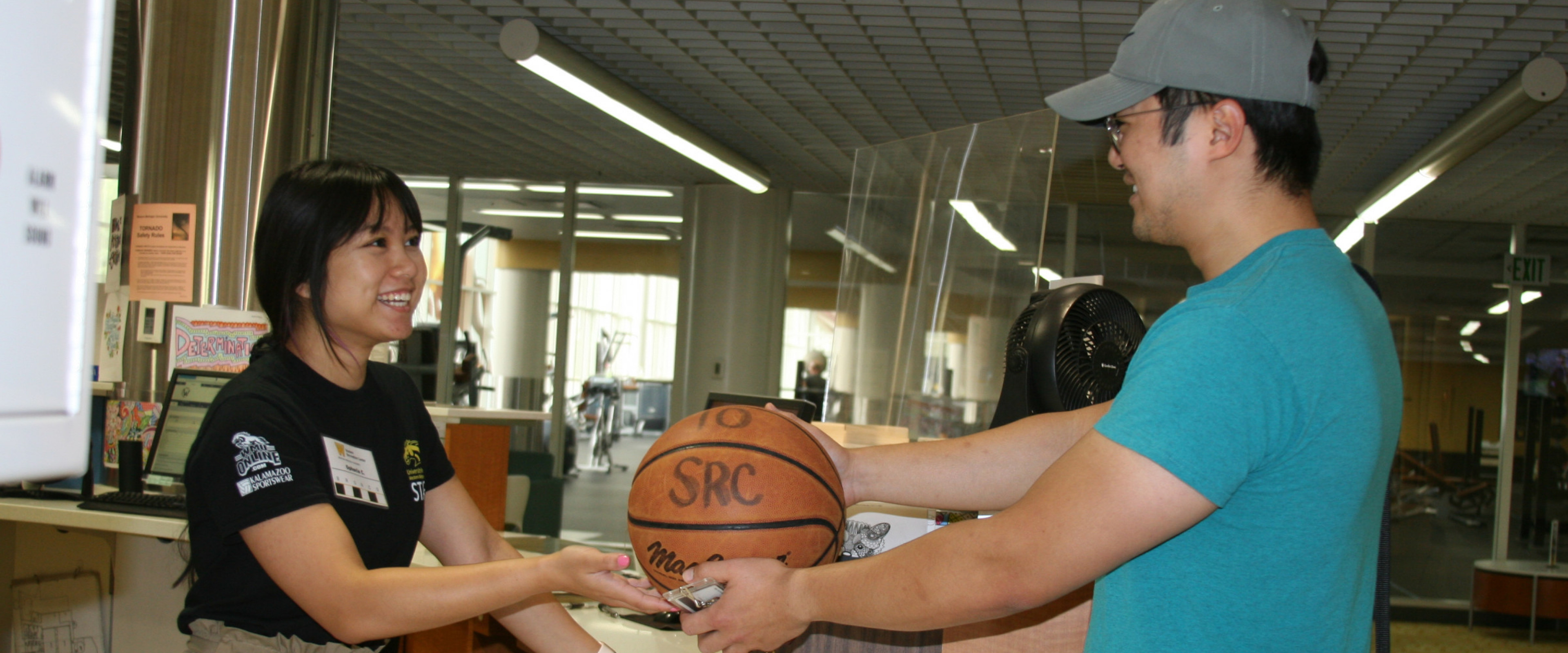 SRC employee working at the service desk checking a basketball out to a patron.
