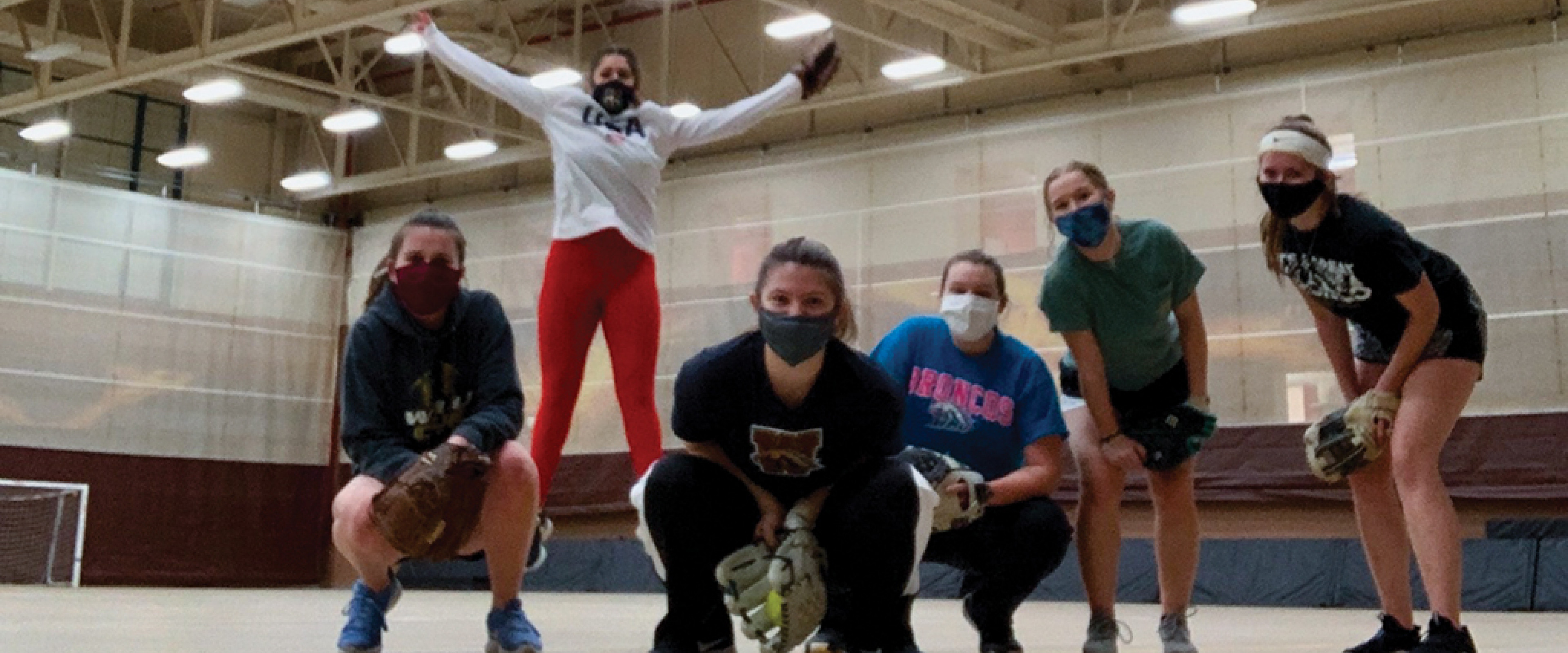 Softball team with masks practicing