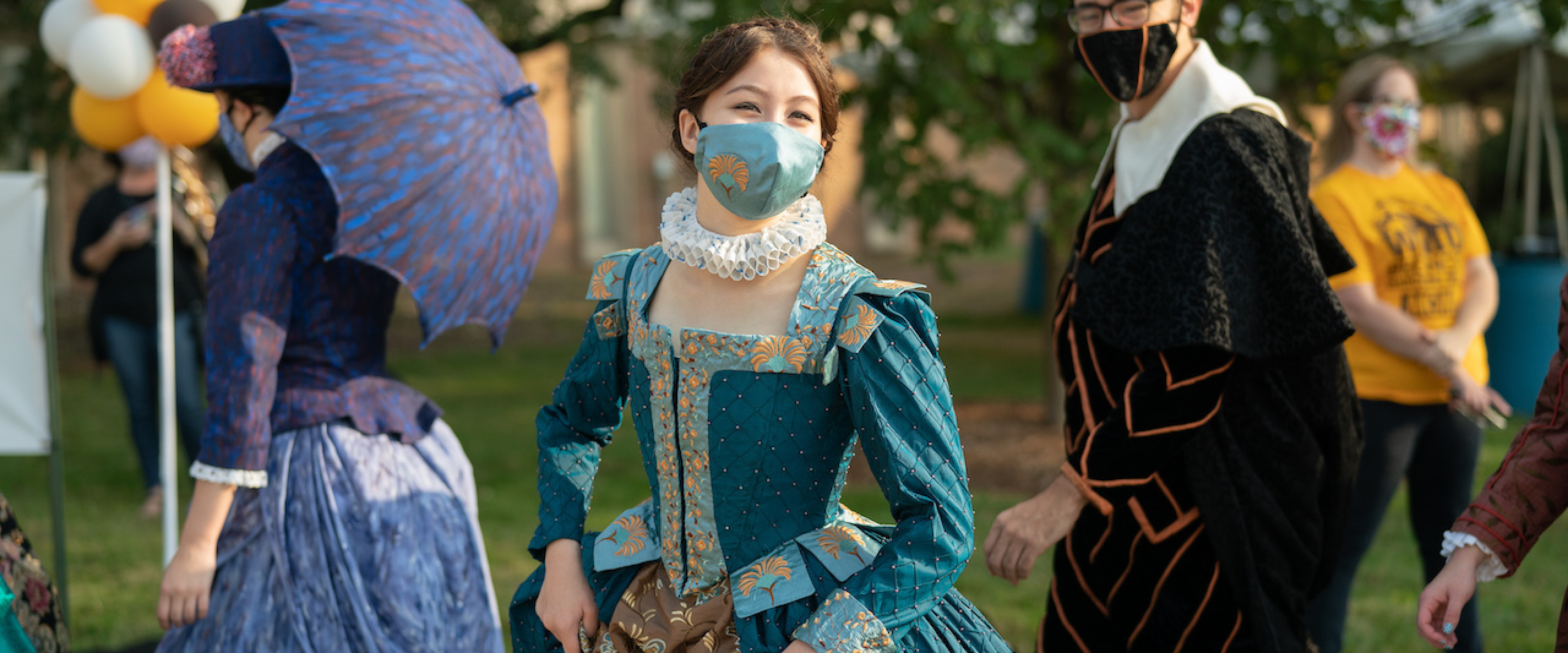 Young woman in teal, Shakespearian dress, wearing a mask while walking outdoors.