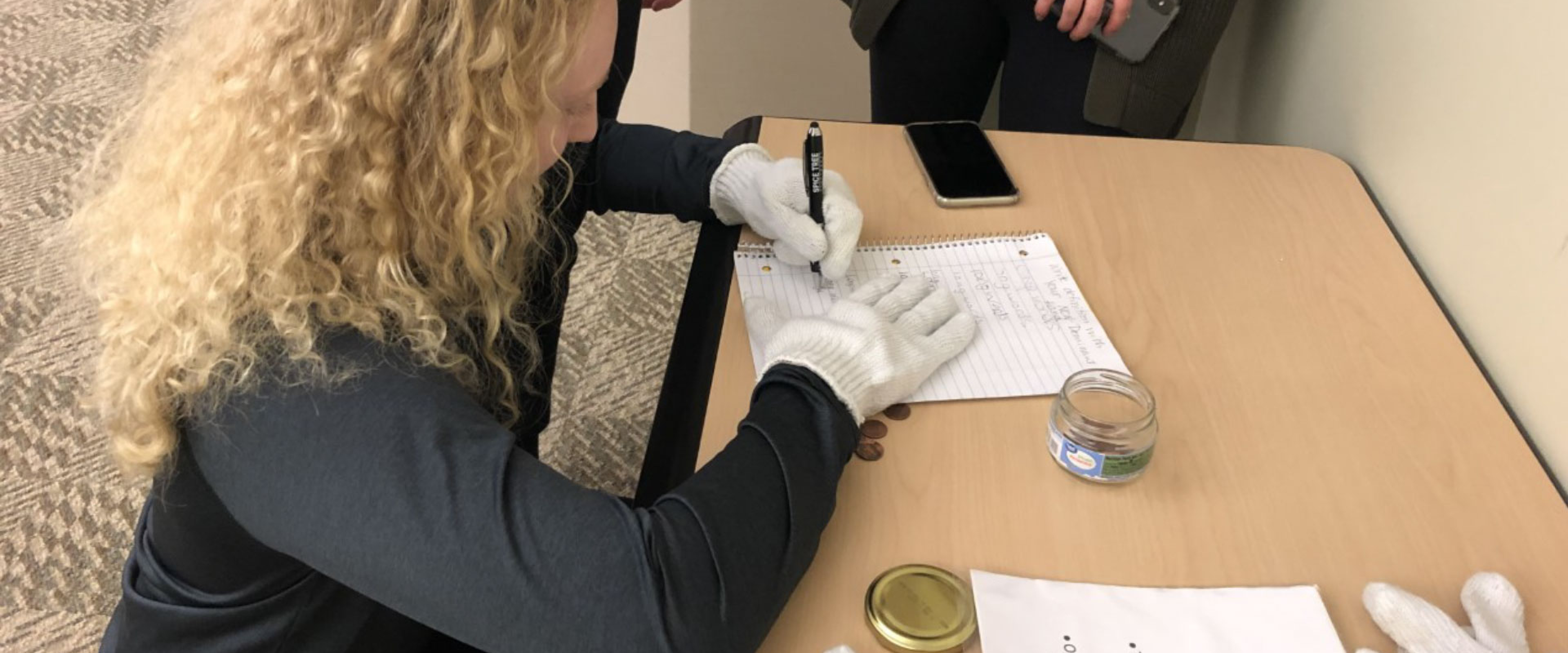 student writing with gloves on