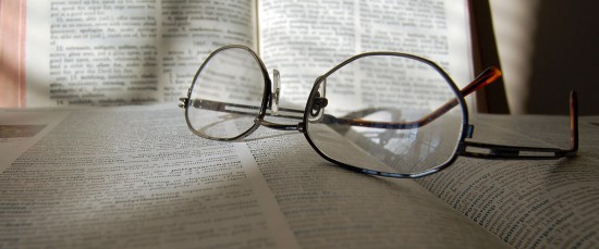 Photo of dictionary with reading glasses.