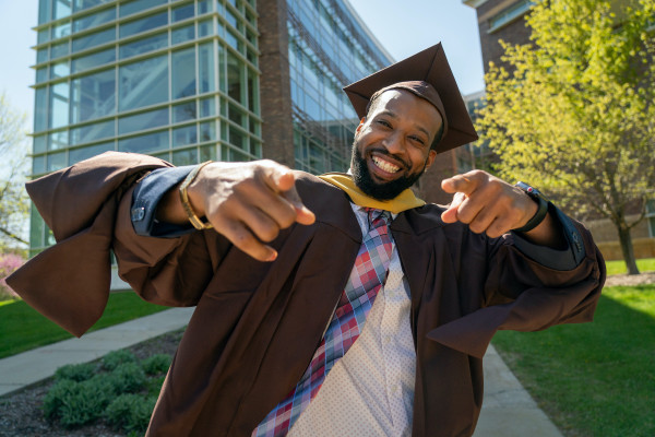 A smiling graduate outside of the College of Health and Human Services