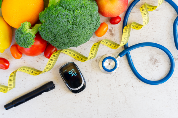 vegetables displayed with a stethoscope, tape measure and diabetes calculator