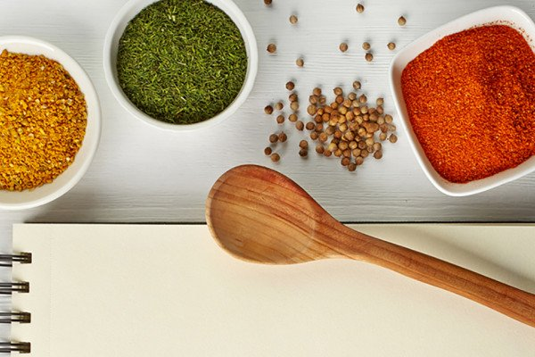 Spices in bowls with a wooden spoon and a notebook under it