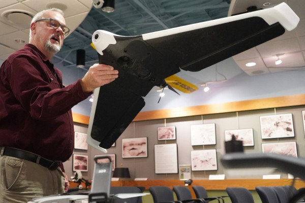 Emerson holds a fixed wing drone.
