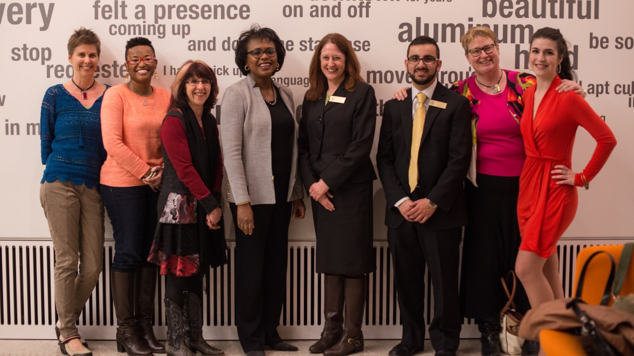 The Raise Your Voice Committee with Anita Hill standing in front of a wall.