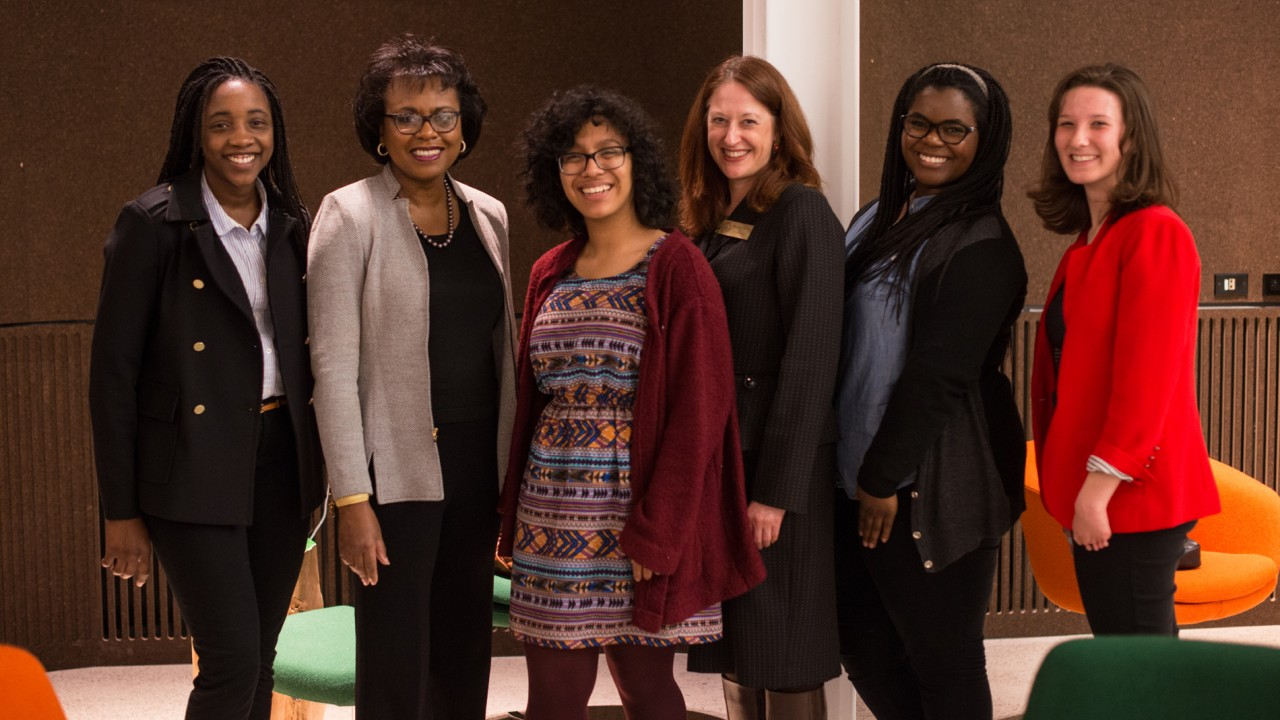 Anita Hill with former dean Carla Koretsky and honors college students standing in front of a white pillar.
