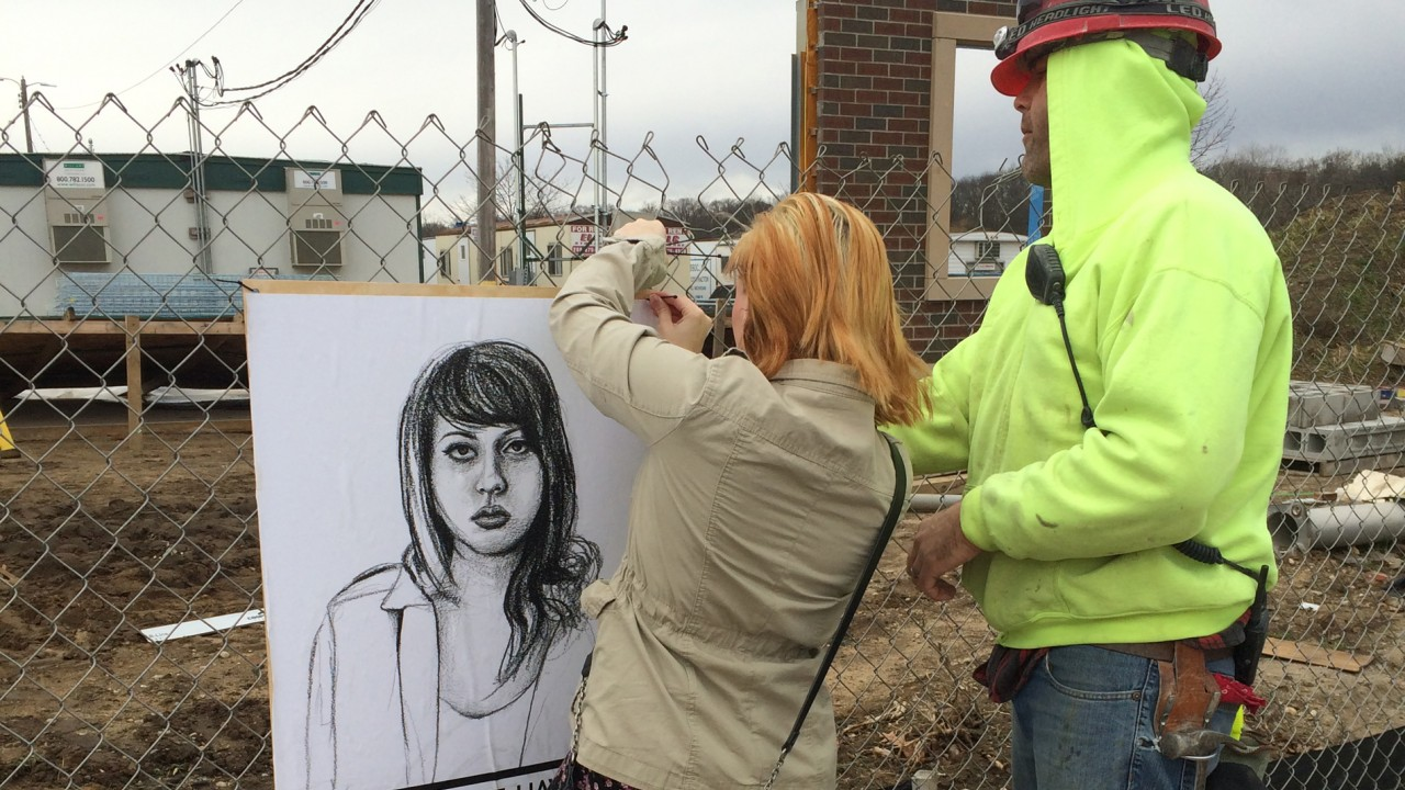 Student hangs a Stop Telling Women to Smile poster on the construction fence.